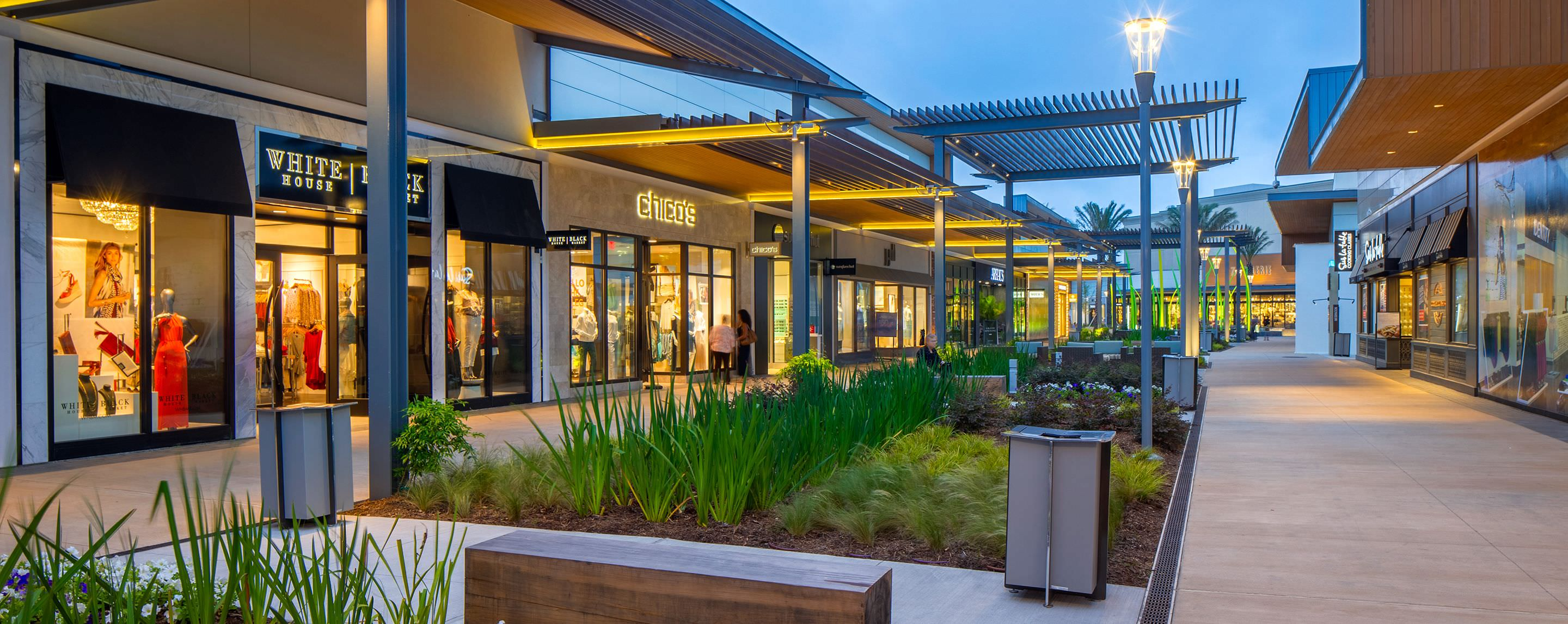 At night, an outdoor walkway is filled with store fronts welcoming shoppers.