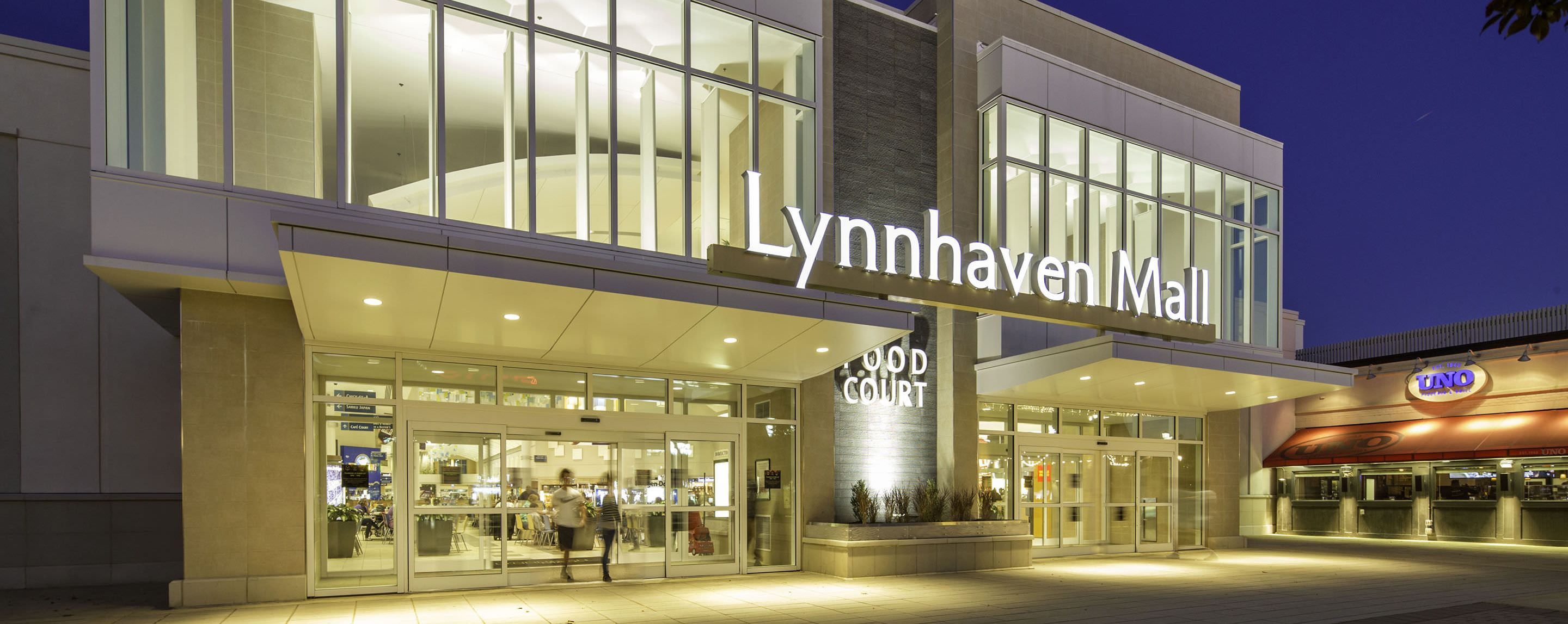 At night, the exterior Lynnhaven Mall sign shines brightly as shoppers leave the property.