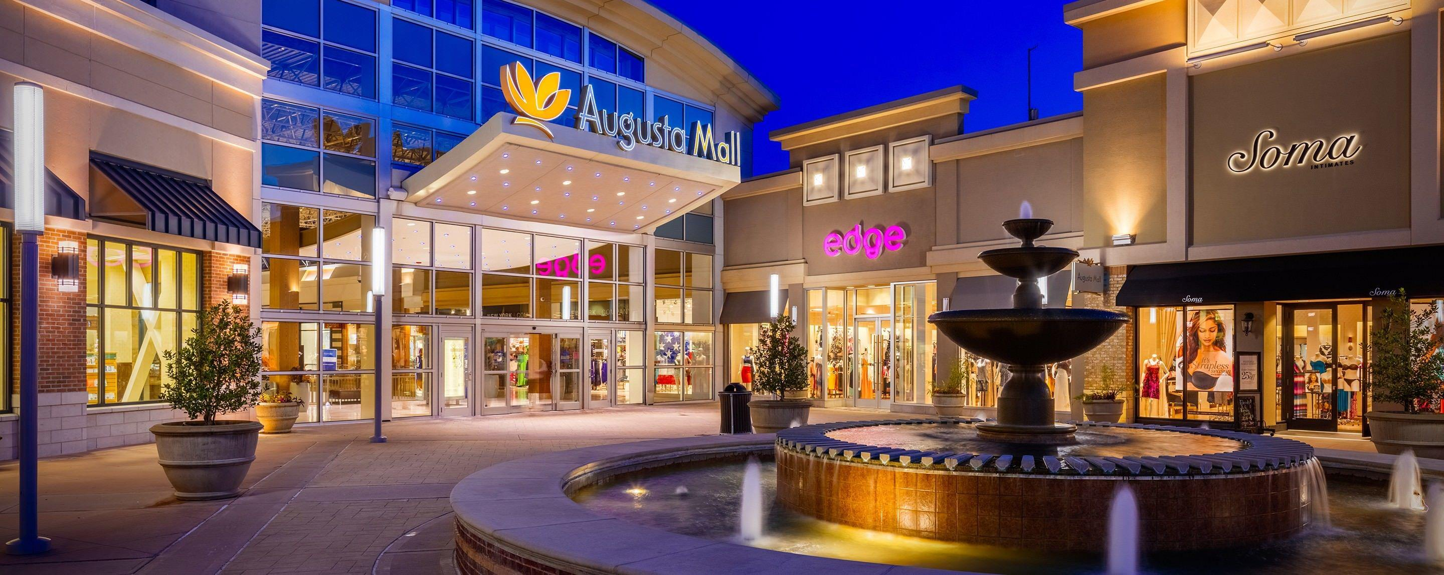 The exterior of the Augusta Mall entrance at night with a running fountain, store fronts, and potted trees.