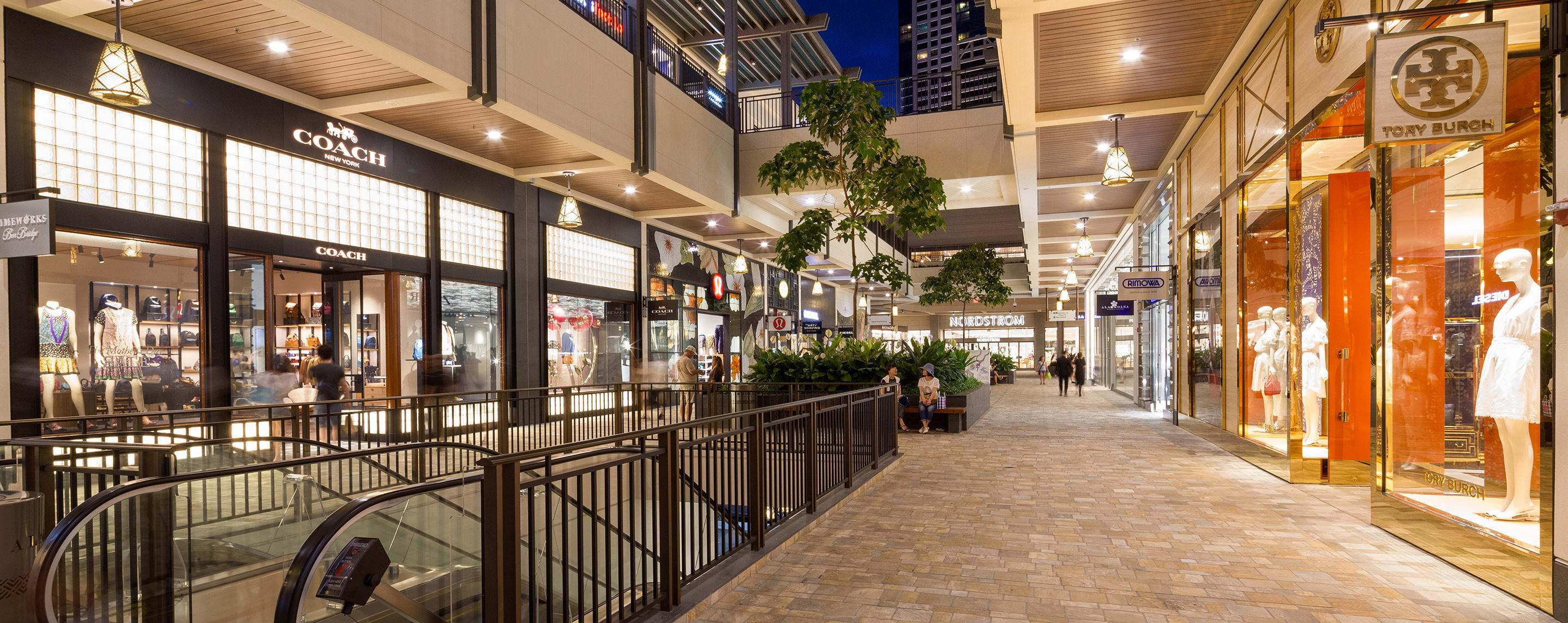 At night, the Ala Moana store fronts light up a walkway for visitors to shop or take a break on a bench.
