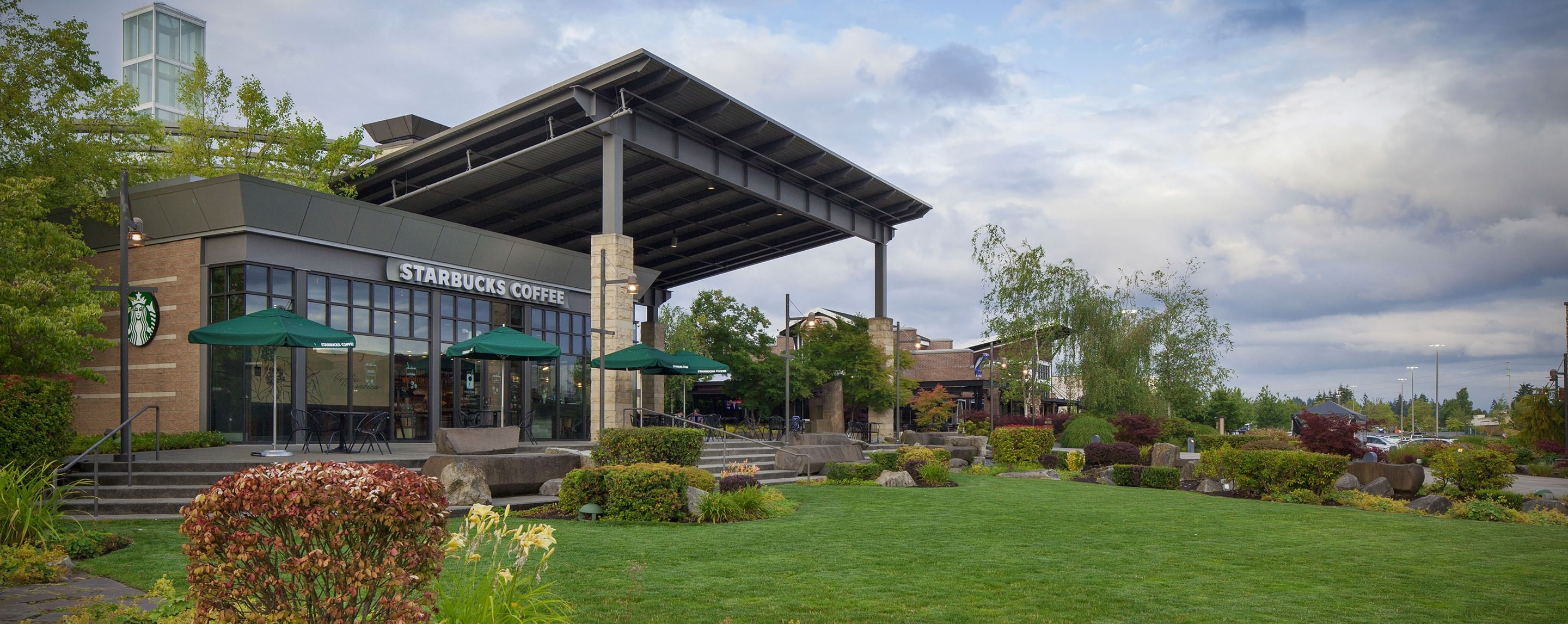 On a sunny day, the Starbucks Coffee at Alderwood overlooks a grassy open space decorated with plants and flowers