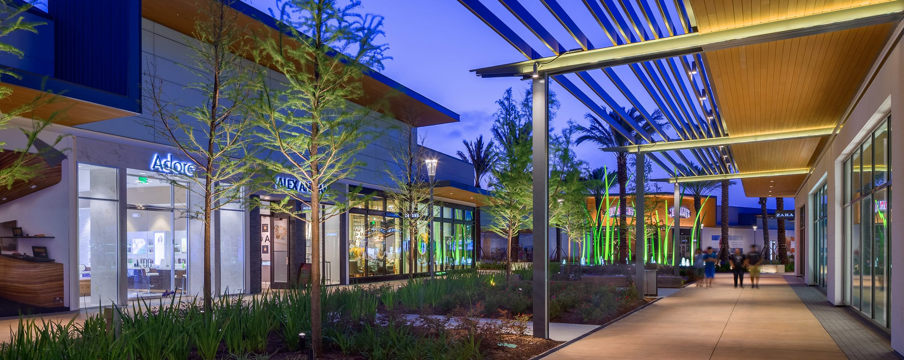 An outside walkway of Baybrook mall is lit up at night for shoppers to look at storefronts, trees, and greenery.