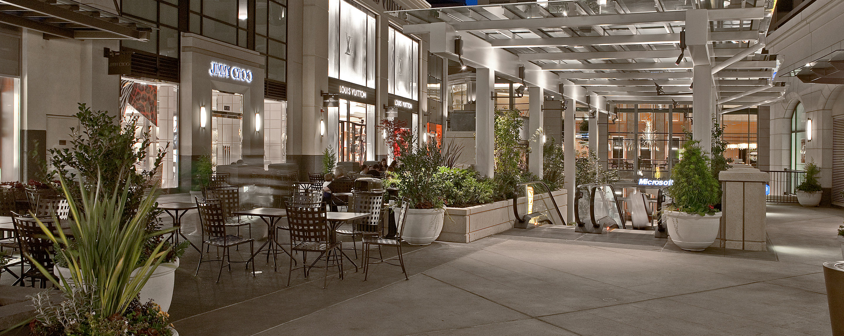 An outdoor common area for shoppers to sit and relax is illuminated at night by storefronts at The Shops at Bravern.