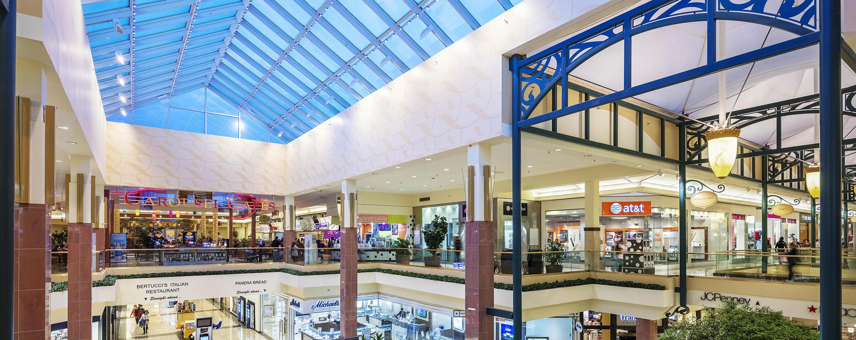 Inside the Shoppes at Buckland Hills atrium, light shines through the sky roof onto the two levels of store fronts.