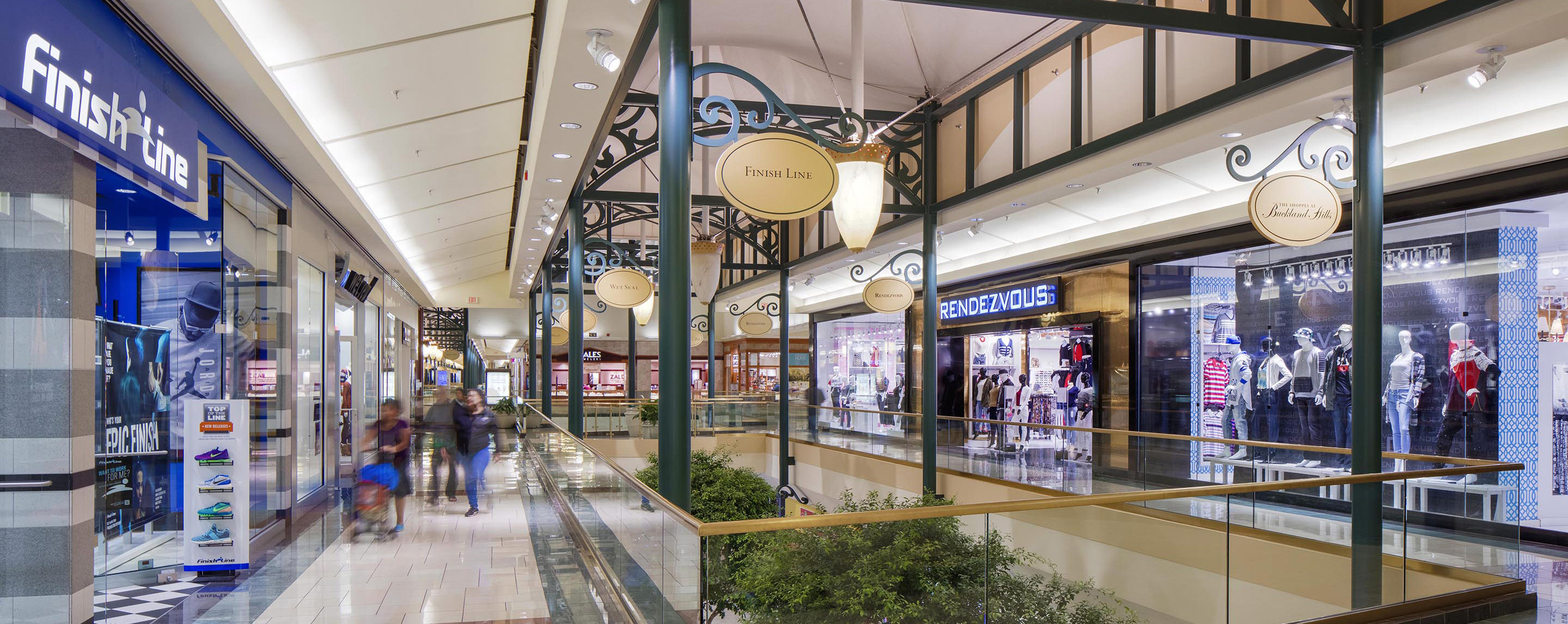 On the upper level of the Shoppes at Buckland Hills, a walkway is lined with store fronts with decorative signs for all the retailers.