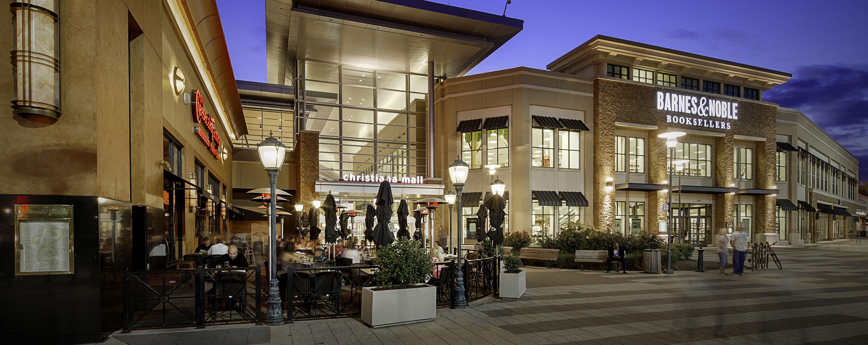 Outside at night, shoppers and diners eat in an outdoor seating area of Cheesecake Factory by the Christiana Mall entrance.