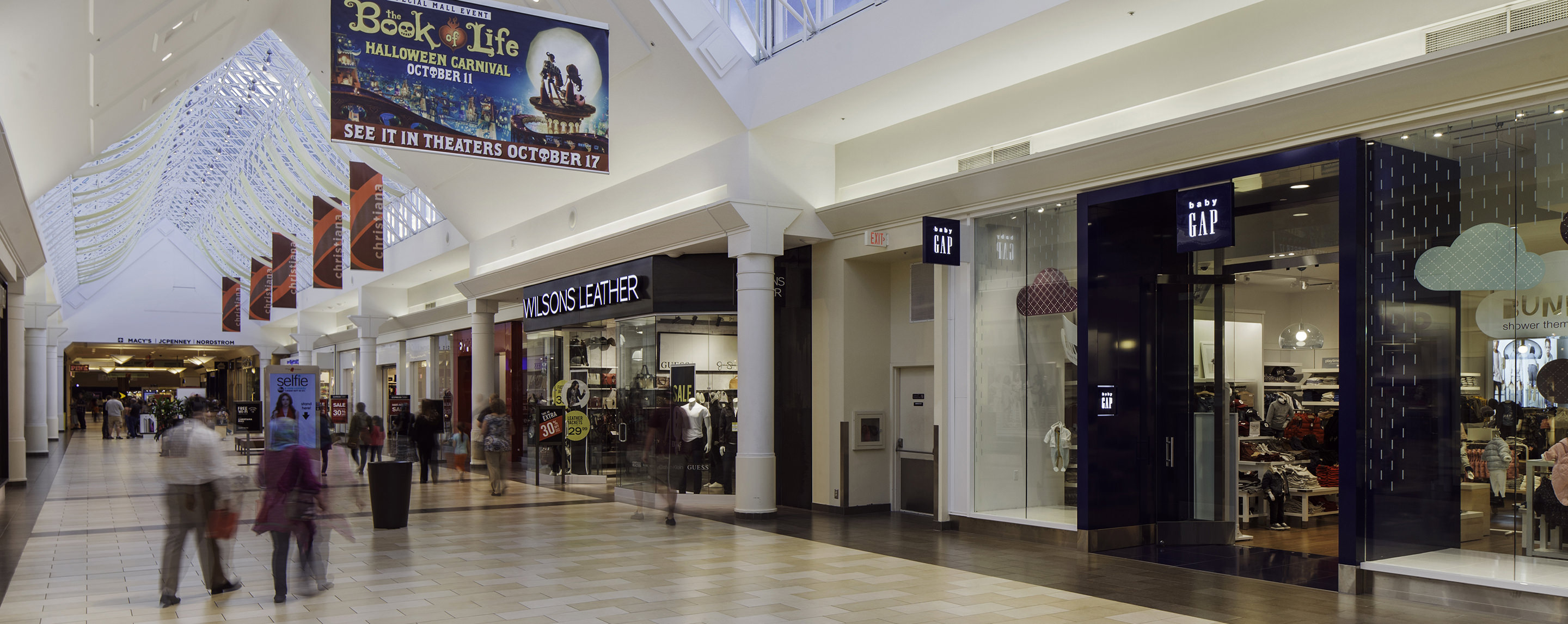 Inside the interior walkway of the Christiana Mall, shoppers look and walk into store fronts.