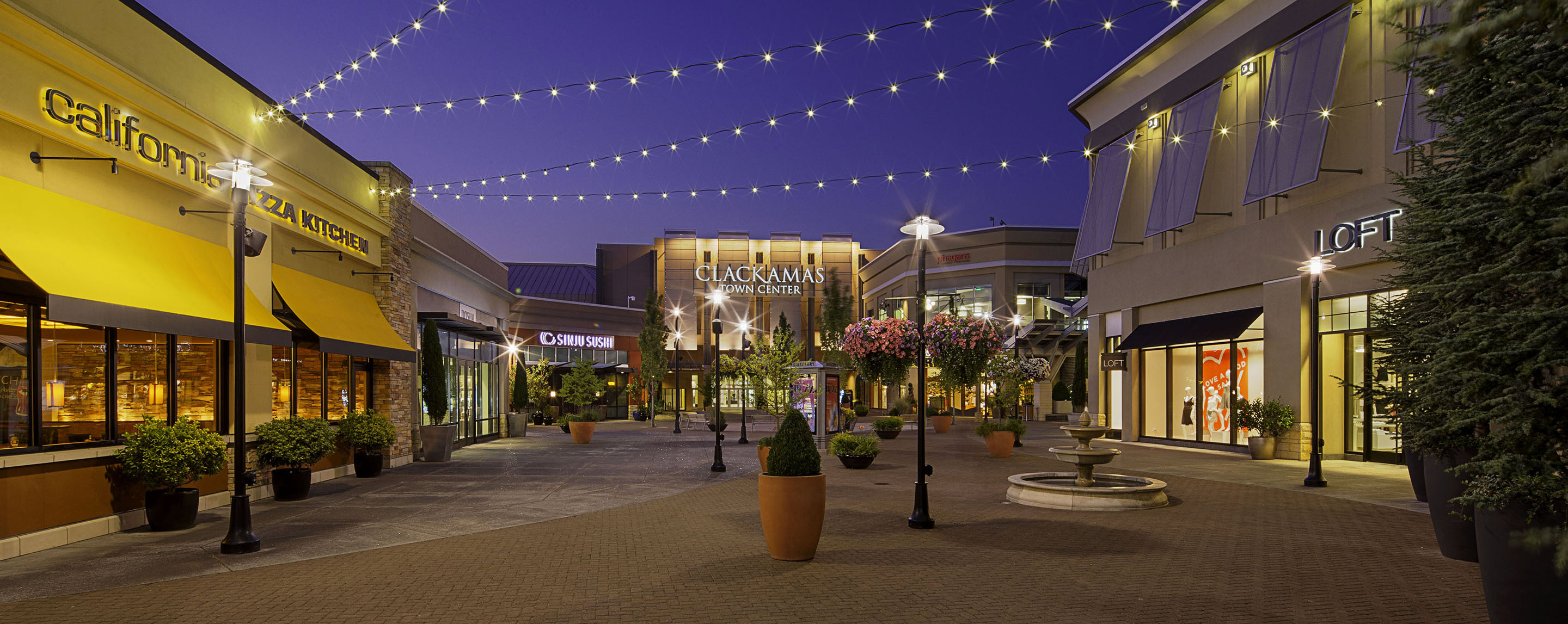 Outside Clackamas Town Center at night, the common area is lit up with string lights and decorated with potted plants, flowers and fountains.