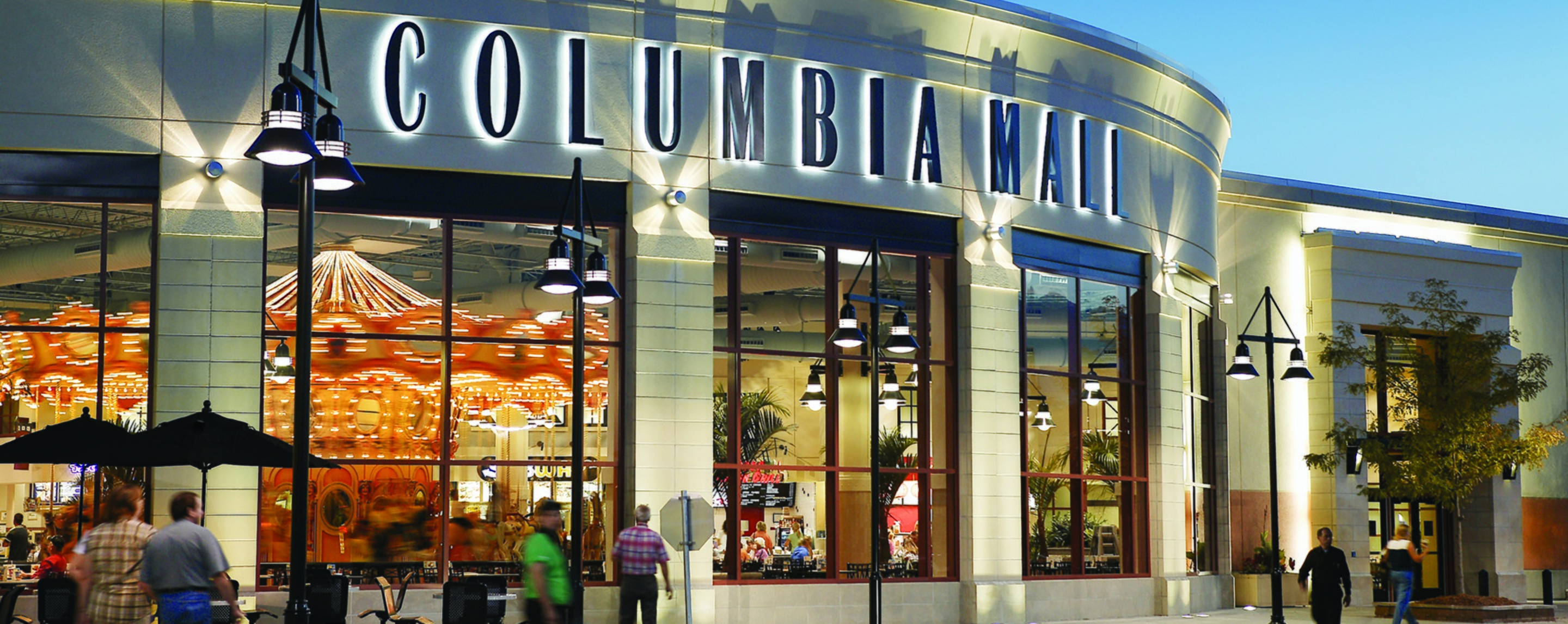 From outside, the Columbia Mall sign lights up at dusk and through the windows you can see a carousel in a common area.