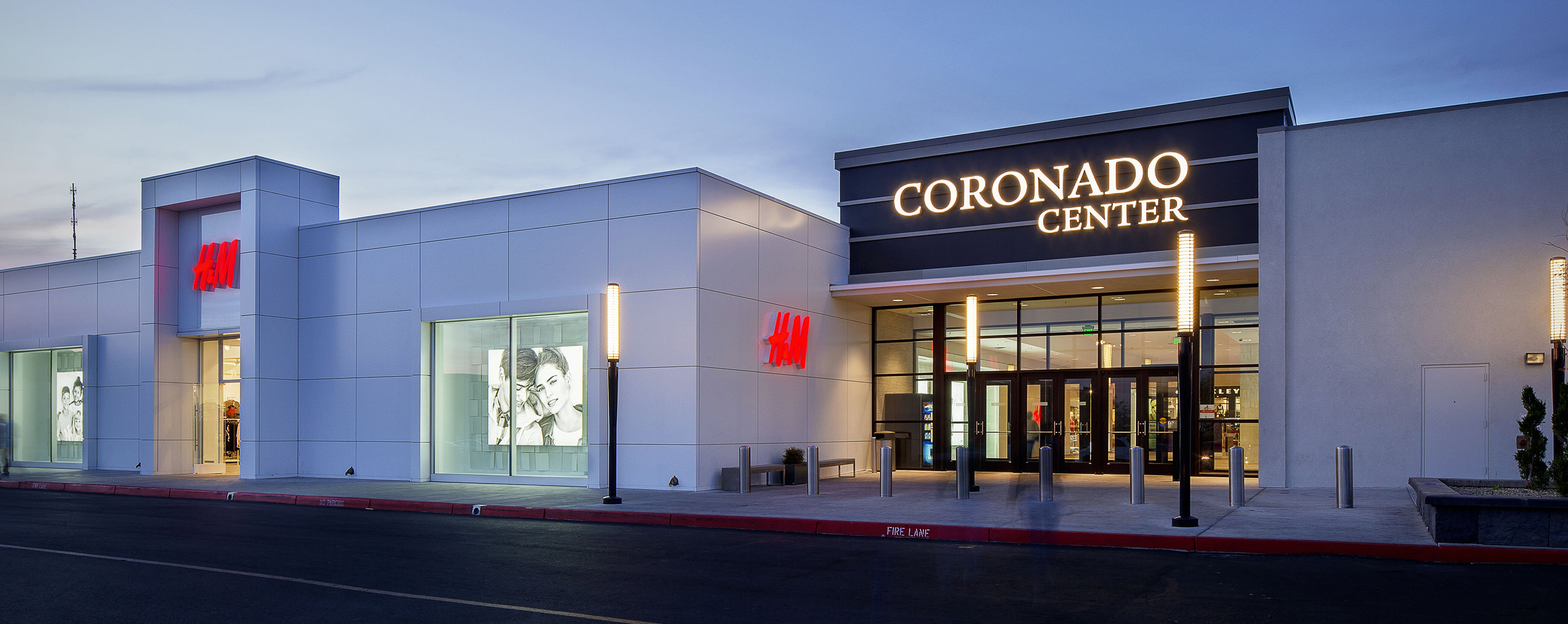 One of the Coronado Center entrances is lit up just after sunset right next to an H&M.