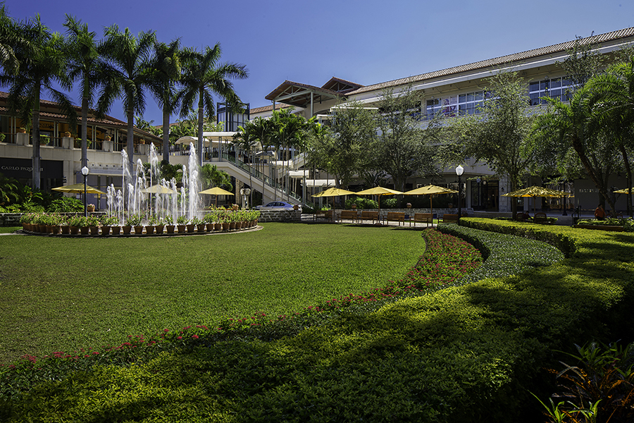 Lush landscaping and a fountain are seen outside the Shops at Merrick Park on a sunny day.