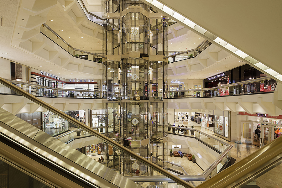Inside the Water Tower Place, the opening from all levels shows the glass elevators surrounded by store fronts.
