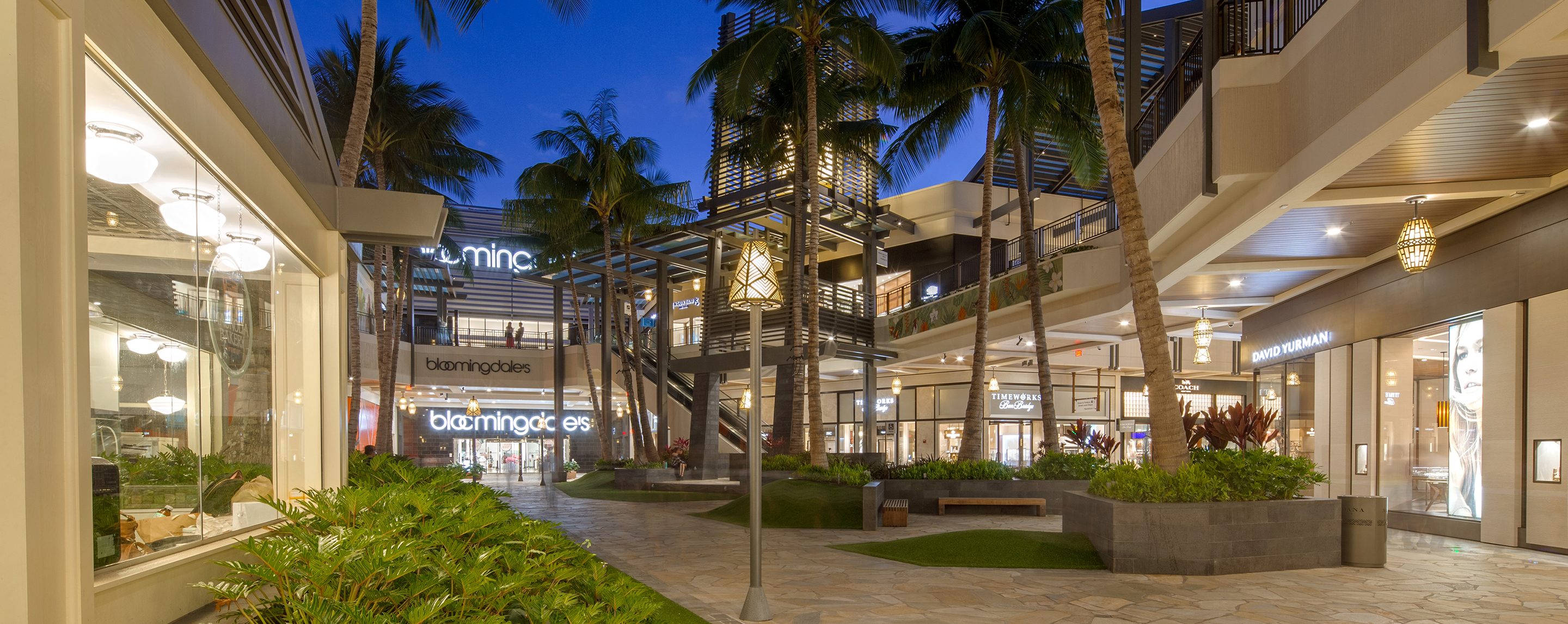 At dusk, an outdoor walkway of a property is lined with lit up store fronts and palm trees.