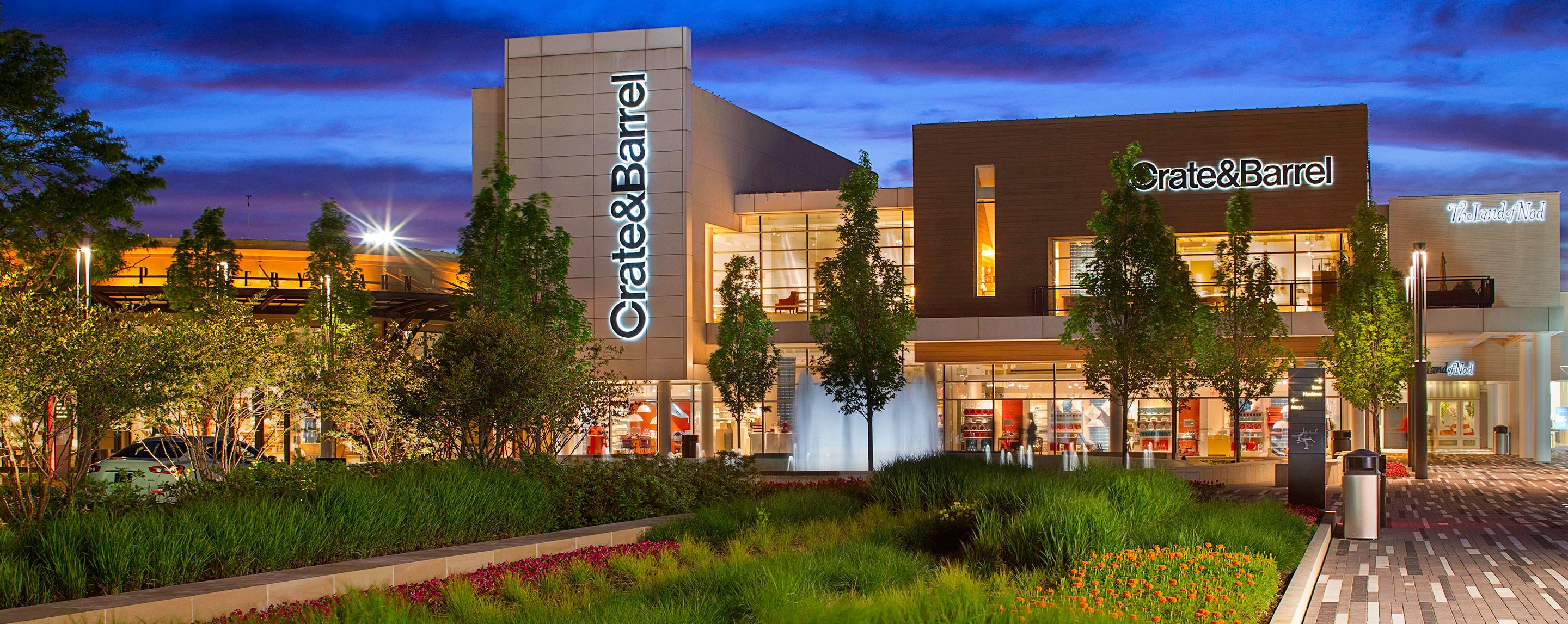 At dusk, Oakbrook Center has beautiful plants and trees in the common area in front of a Crate and Barrel store.