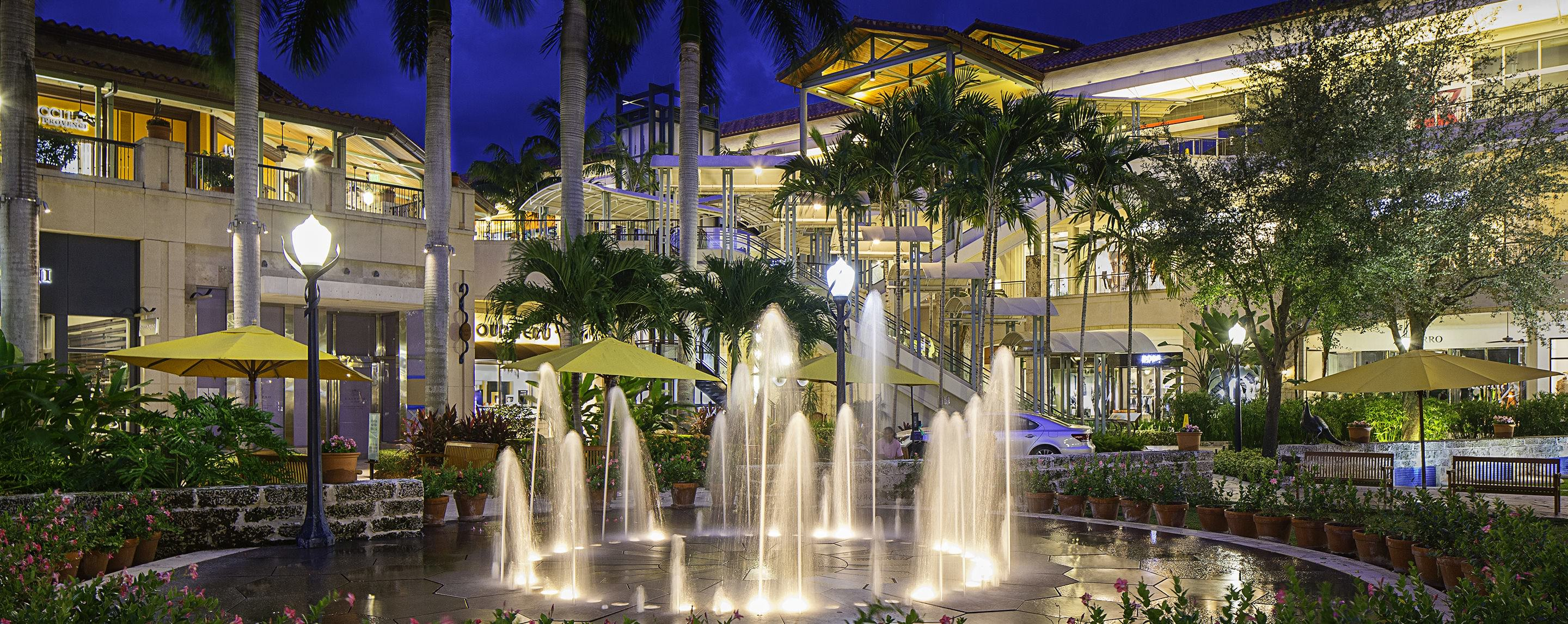 At night, a property is beautifully lit up in a store front lined outdoor walkway decorated with fountains and trees.