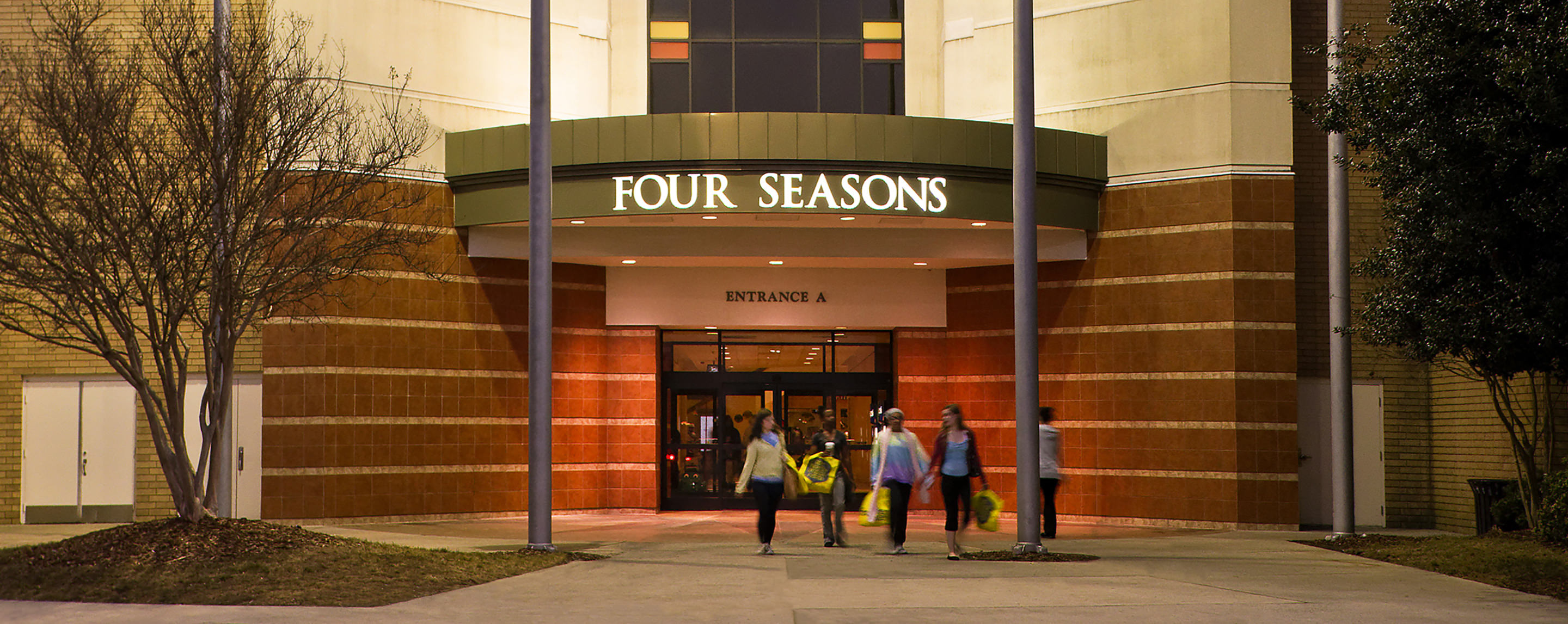 A group of shoppers exit the Four Season Town Center holding shopping bags at night as the property sign is lit up.