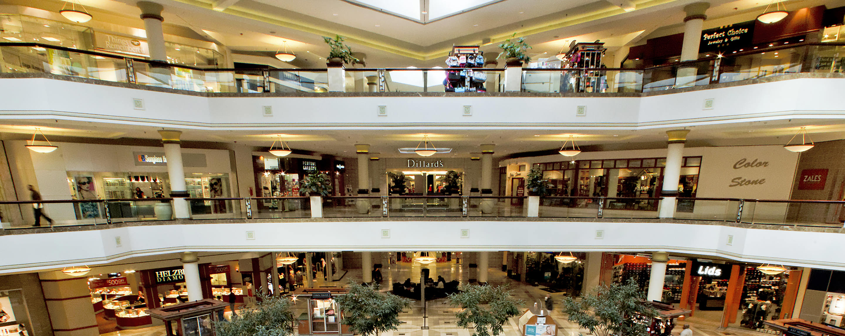 Looking across the interior atrium, you can see three levels of store fronts decorated with potted greenery and hanging lamps.