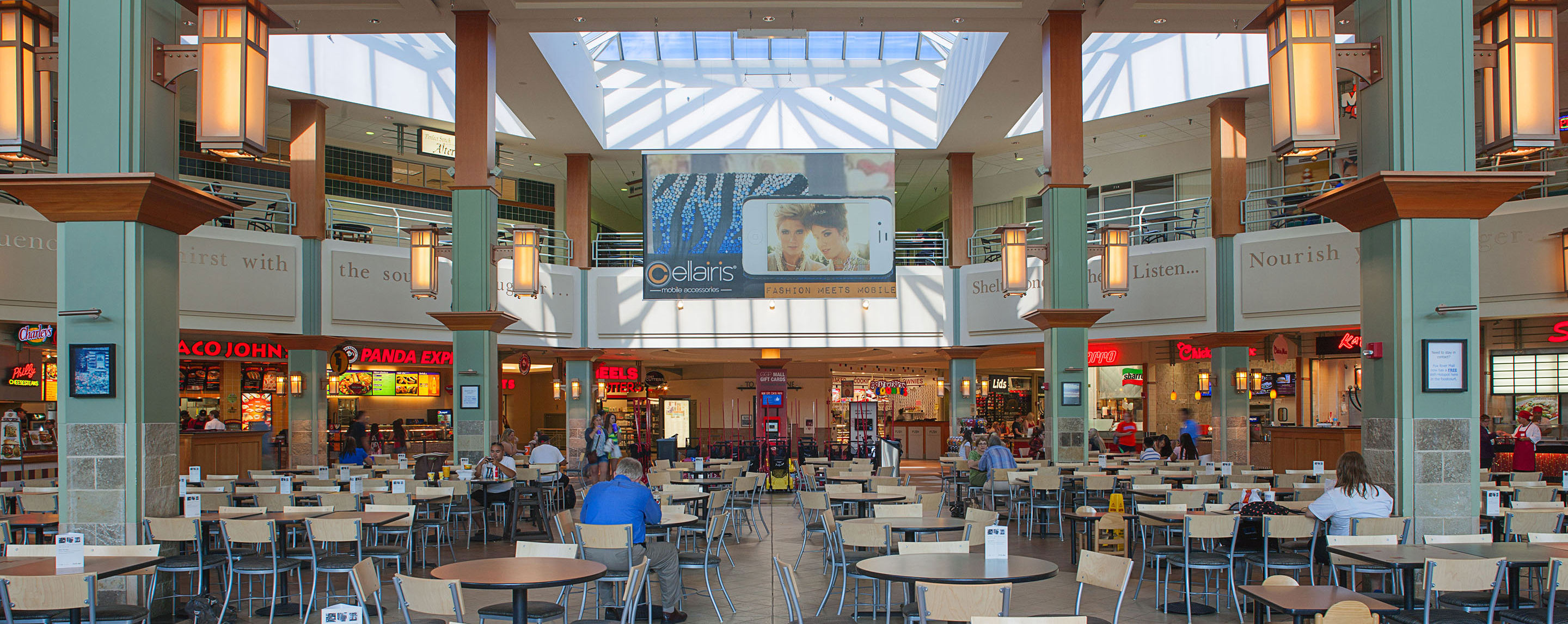 Inside the Fox River Mall food court, shoppers sit, eat, and relax in the common area filled with tables and chairs.