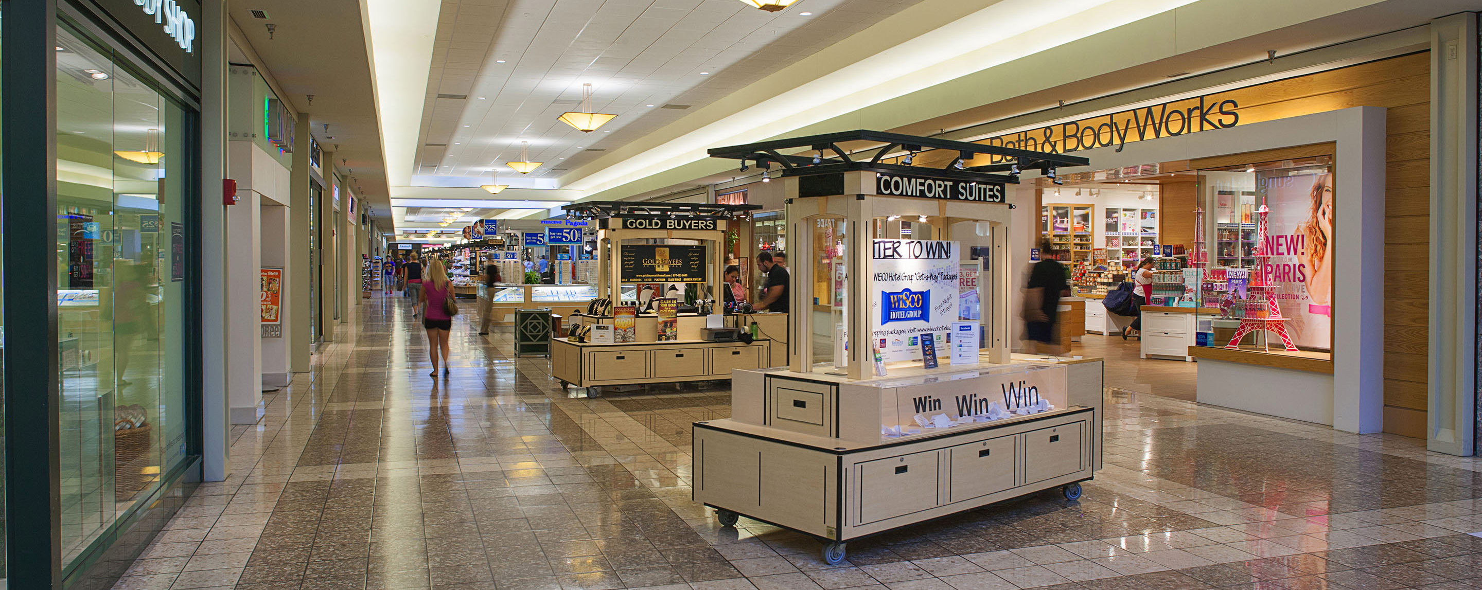 Inside a Fox River Mall walkway, kiosks fill the common area as shoppers walk by and browse at store fronts.
