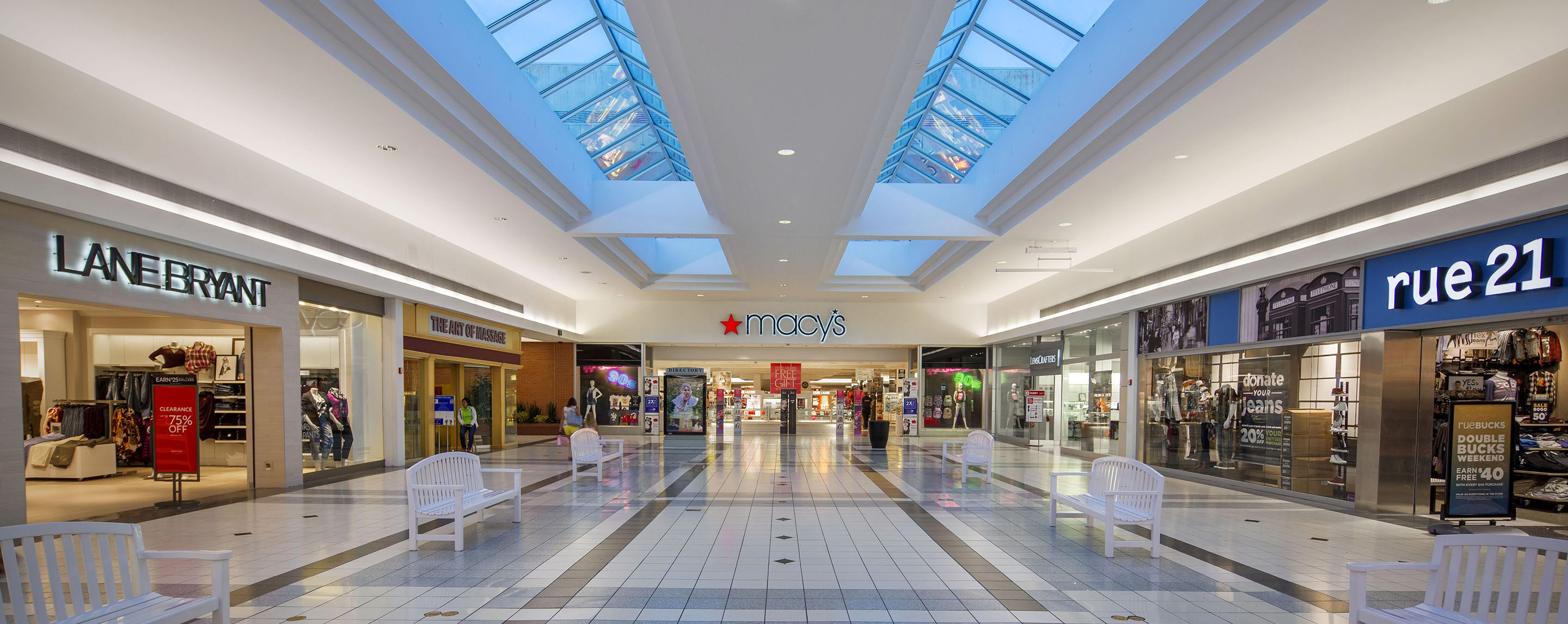 A Glenbrook Square interior open walkway is bright from the skylights and offers several benches for shoppers to take a rest.