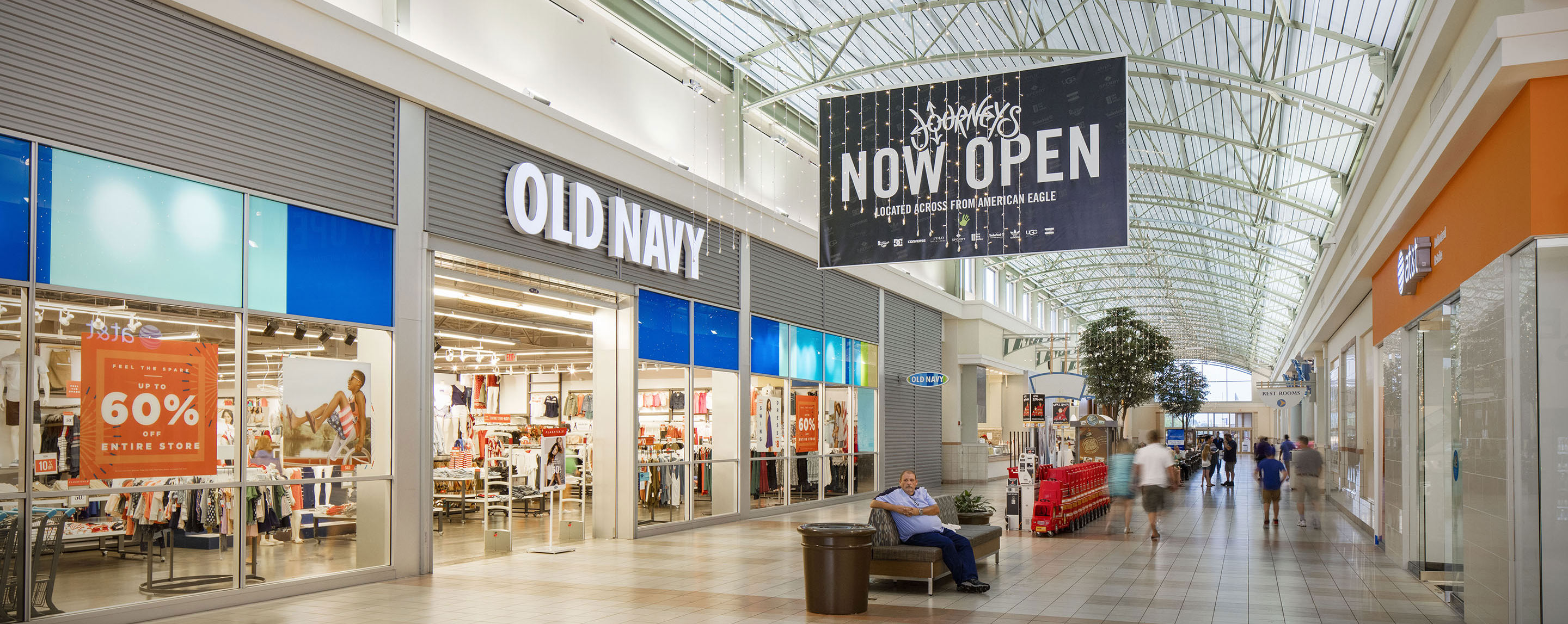 Shoppers at the Greenwood Mall walk past Old Navy as natural light shines through the glass ceiling.