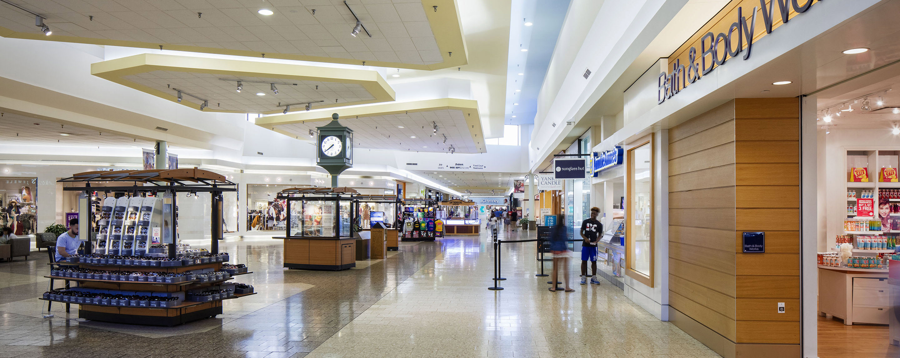 The interior of the Greenwood Mall has shoppers going in and out of store fronts and is also lined with a variety of kiosks in the common area.