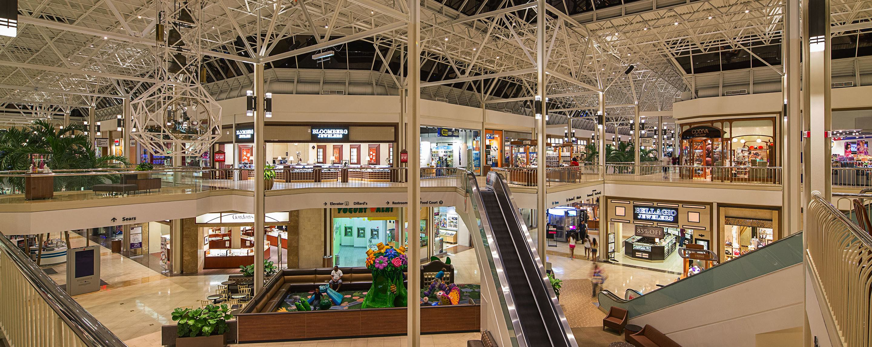The indoor Hulen Mall atrium is lit up at night, lined with store fronts and has a play area for families on the lowest level.