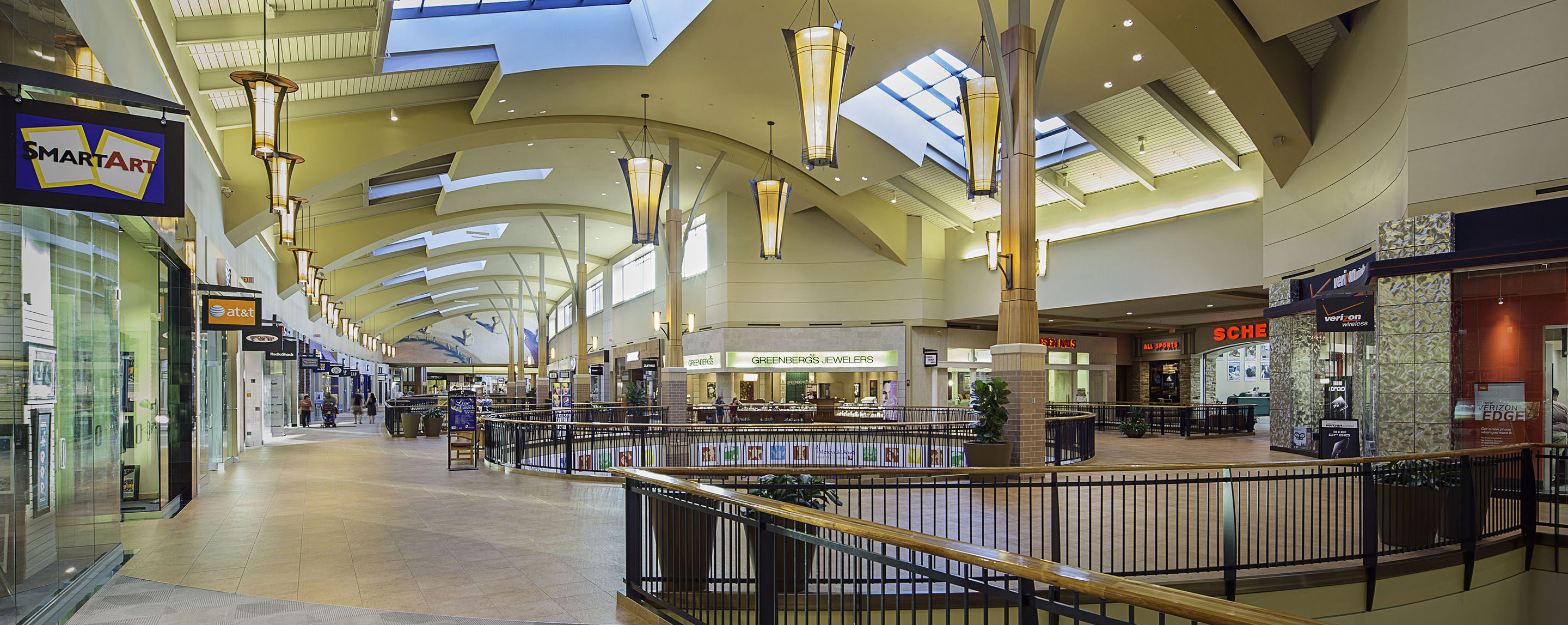 An upper level common area at the Jordan Creek Town Center is decorated with potted plants next to store fronts.
