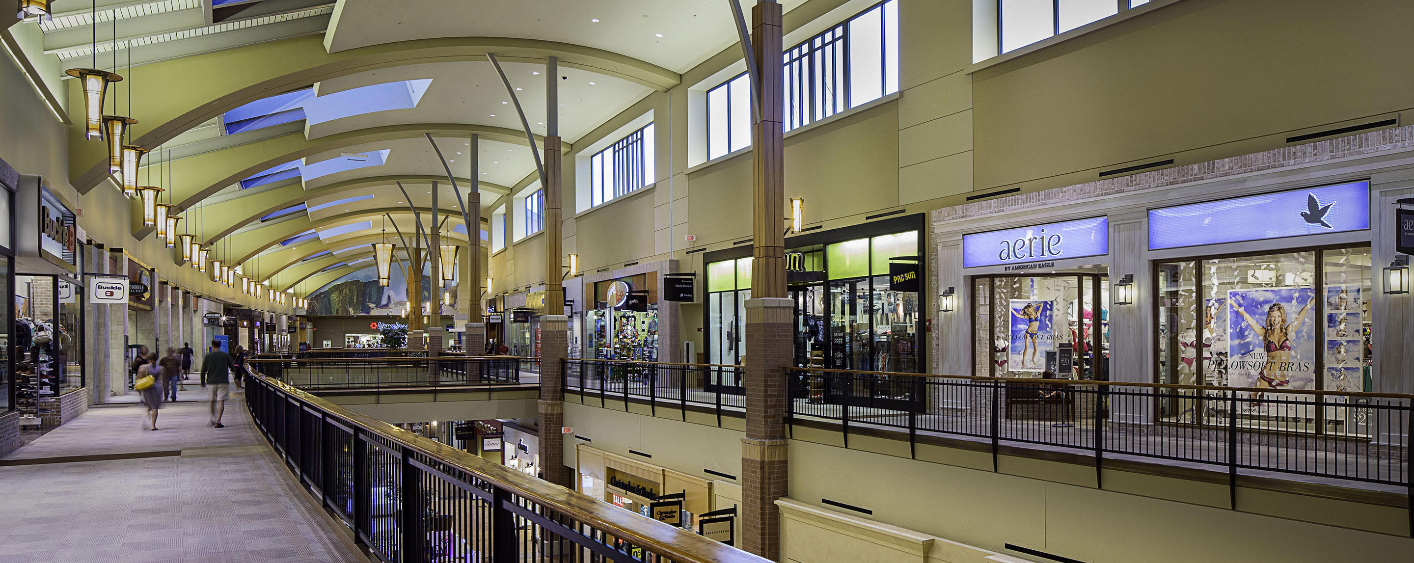 The upper level interior walkway of Jordan Creek Town Center is lined with store fronts as shoppers walk by.