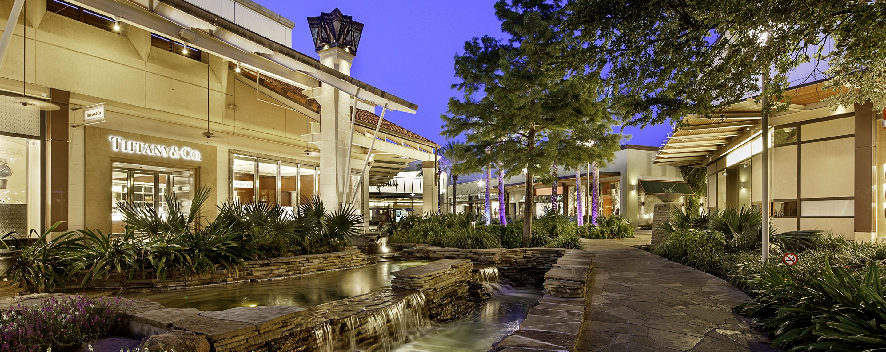 Store fronts light up the exterior walkway at The Shops at La Cantera during the night illuminating the picturesque landscape.