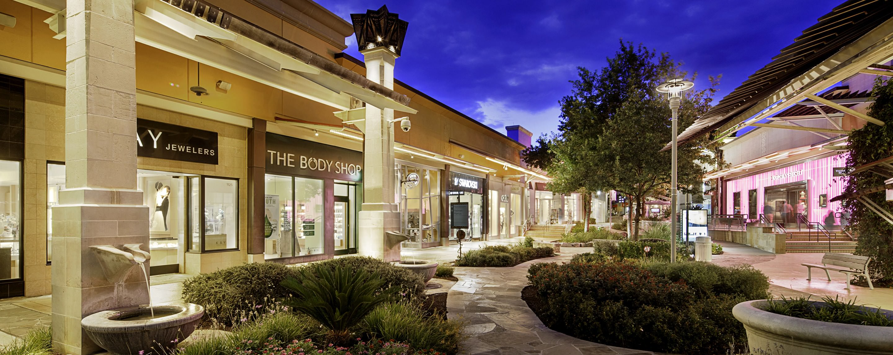 Storefronts at The Shops at La Cantera light up the surrounding area and lush landscaping.