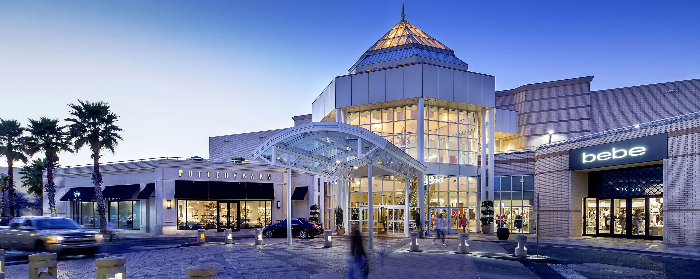 At dusk, the exterior of the Mall of Louisiana is brightly lit up as shoppers enter the building.