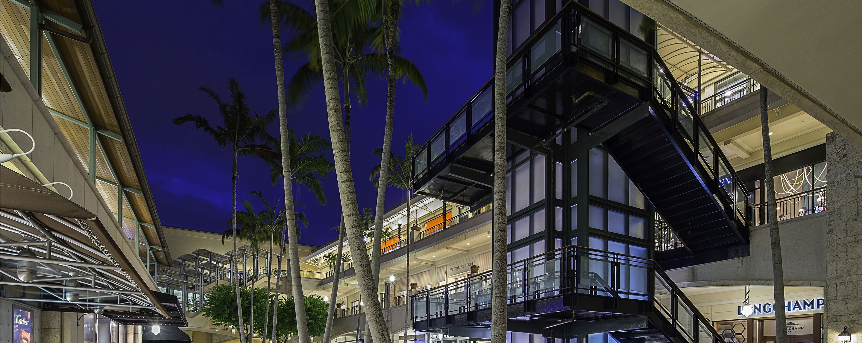 At Shops at Merrick Park, three levels of stores surround an outdoor walkway lined with palm trees.