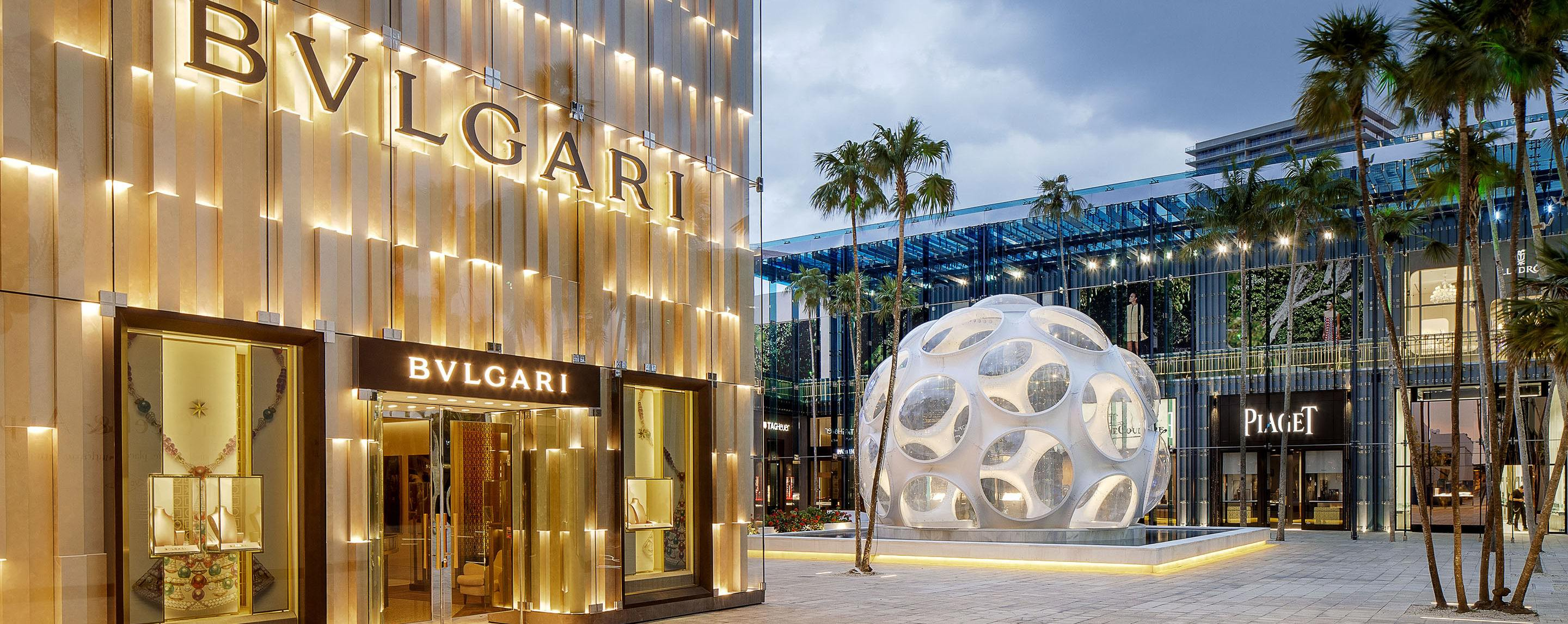 In a common area outside of the Miami Design District, you see lit up store fronts, a large artistic fountain, and numerous palm trees.