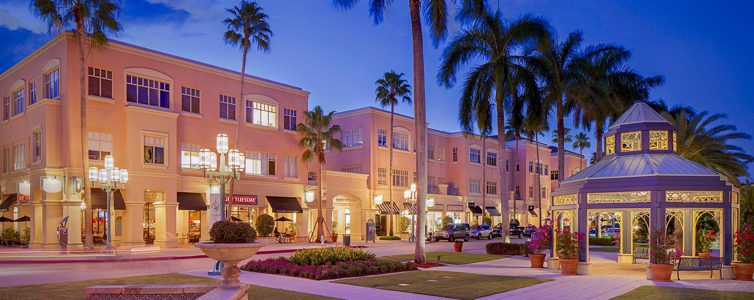 Storefronts and lamp posts line the exterior of Mizner Park at night illuminating the surrounding area.