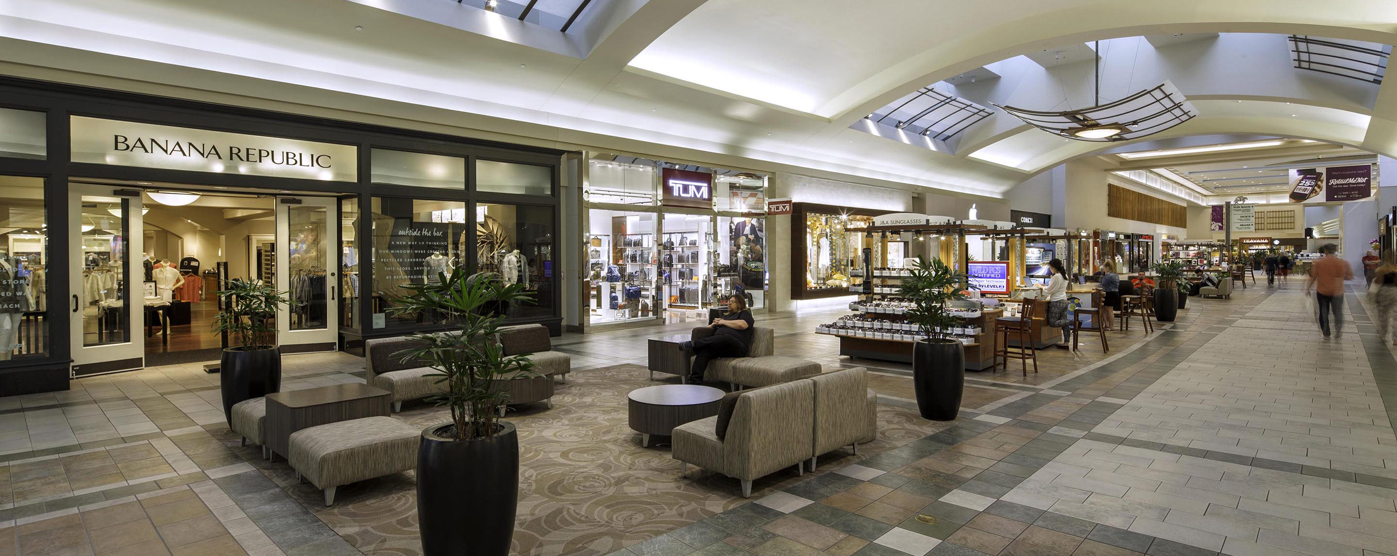 Inside Oxmoor Center, the main walkway is filled with kiosks, seating areas, and storefronts