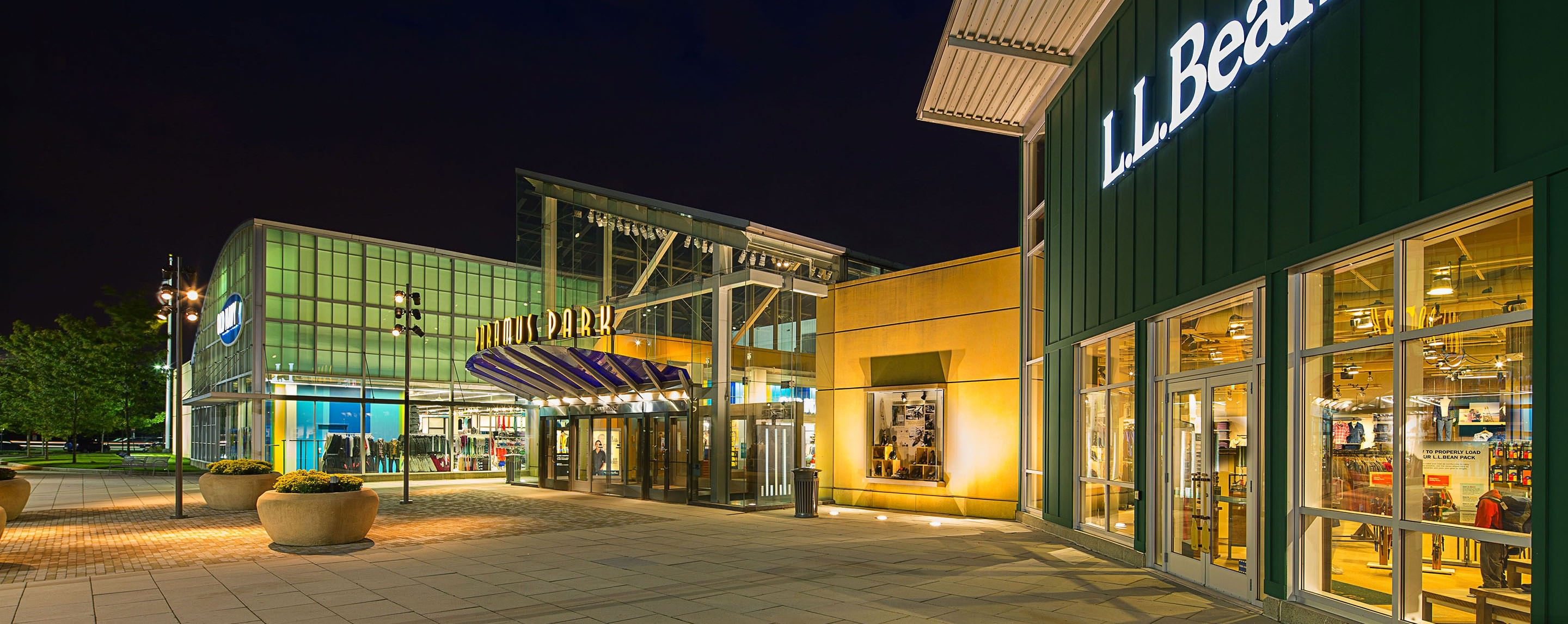 At night, an exterior entrance and other storefronts at Paramus Park are lit up with outdoor lighting