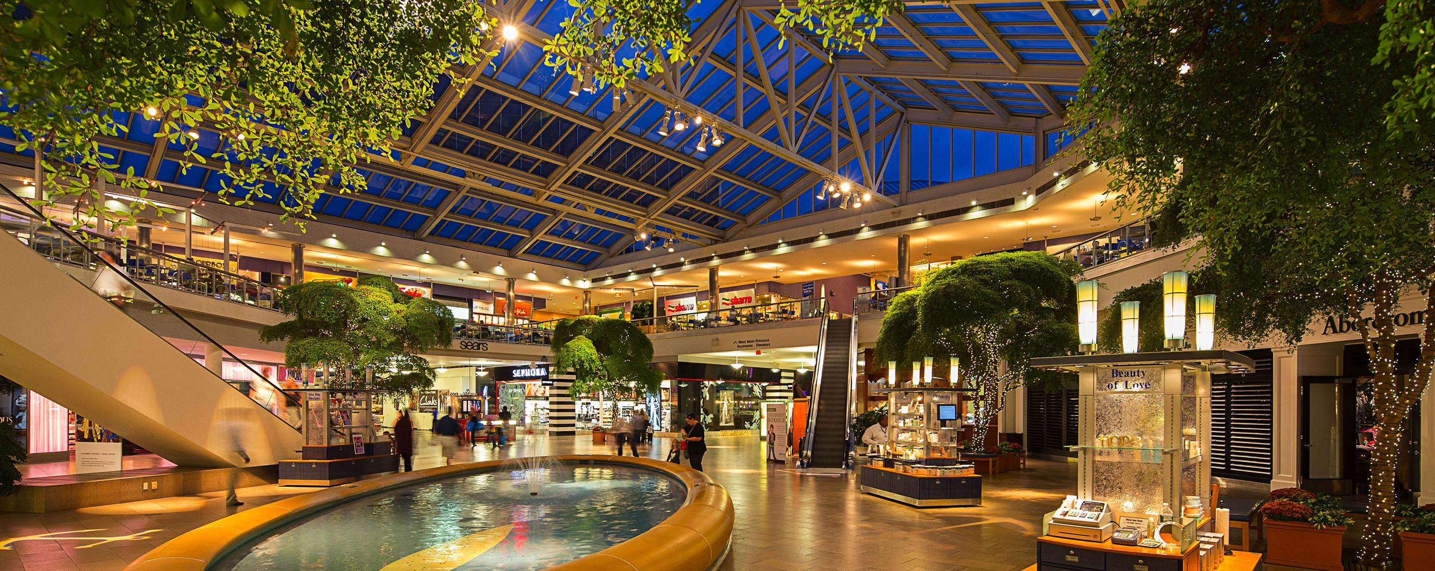 Skylights let shoppers see the night sky at Paramus Park, while a fountain and trees decorate the interior near kiosks and storefronts