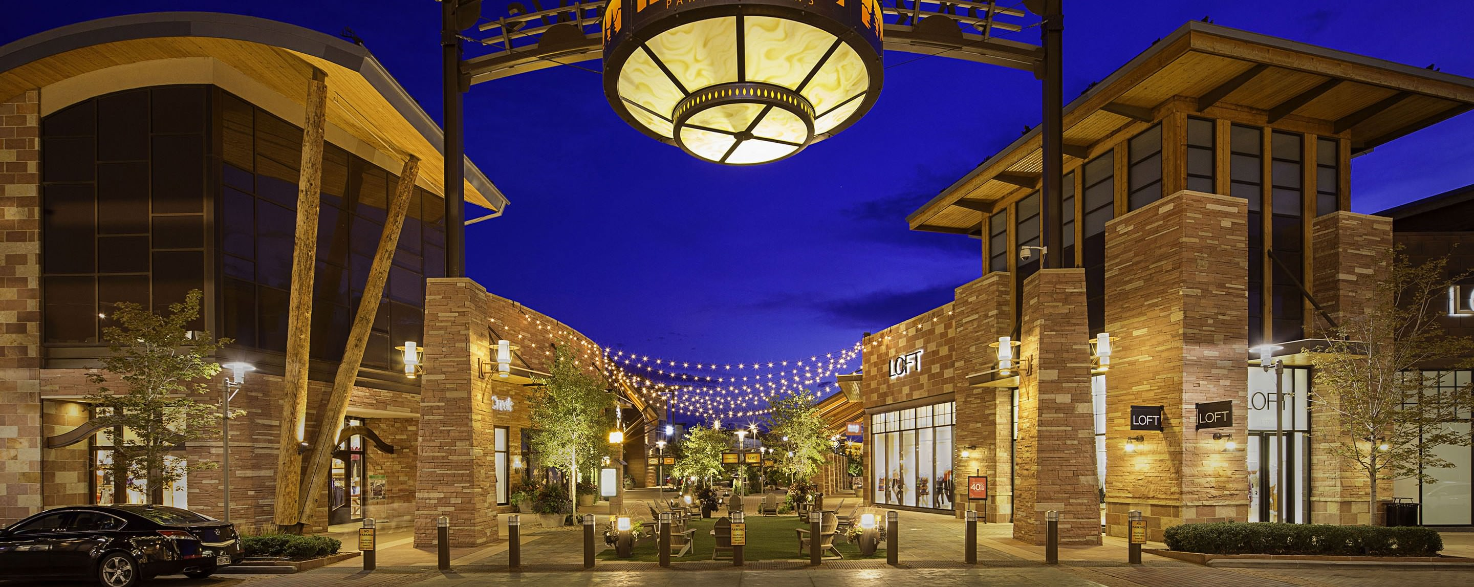 Outside at night, different kinds of lights lead shoppers into the Park Meadows entrance and store fronts.
