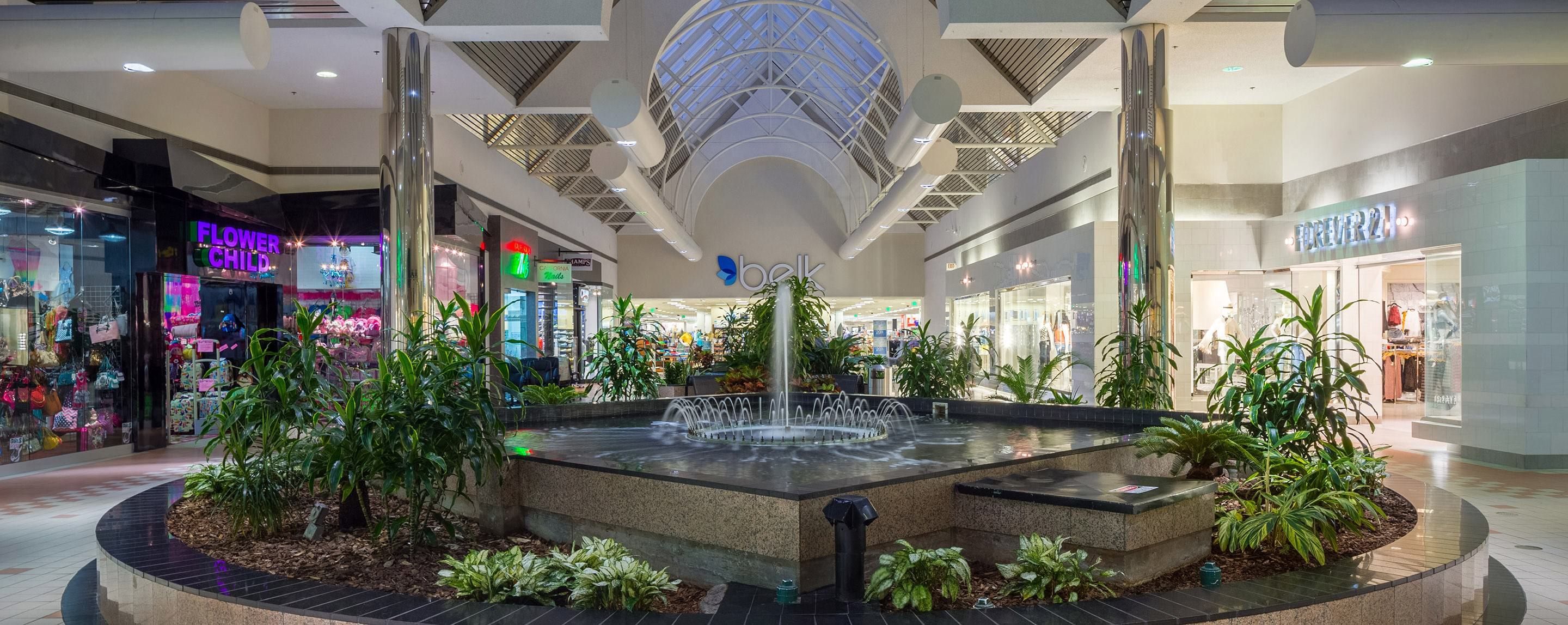 In a common area of Pecanland Mall, a running fountain with plants is surrounded by store fronts.