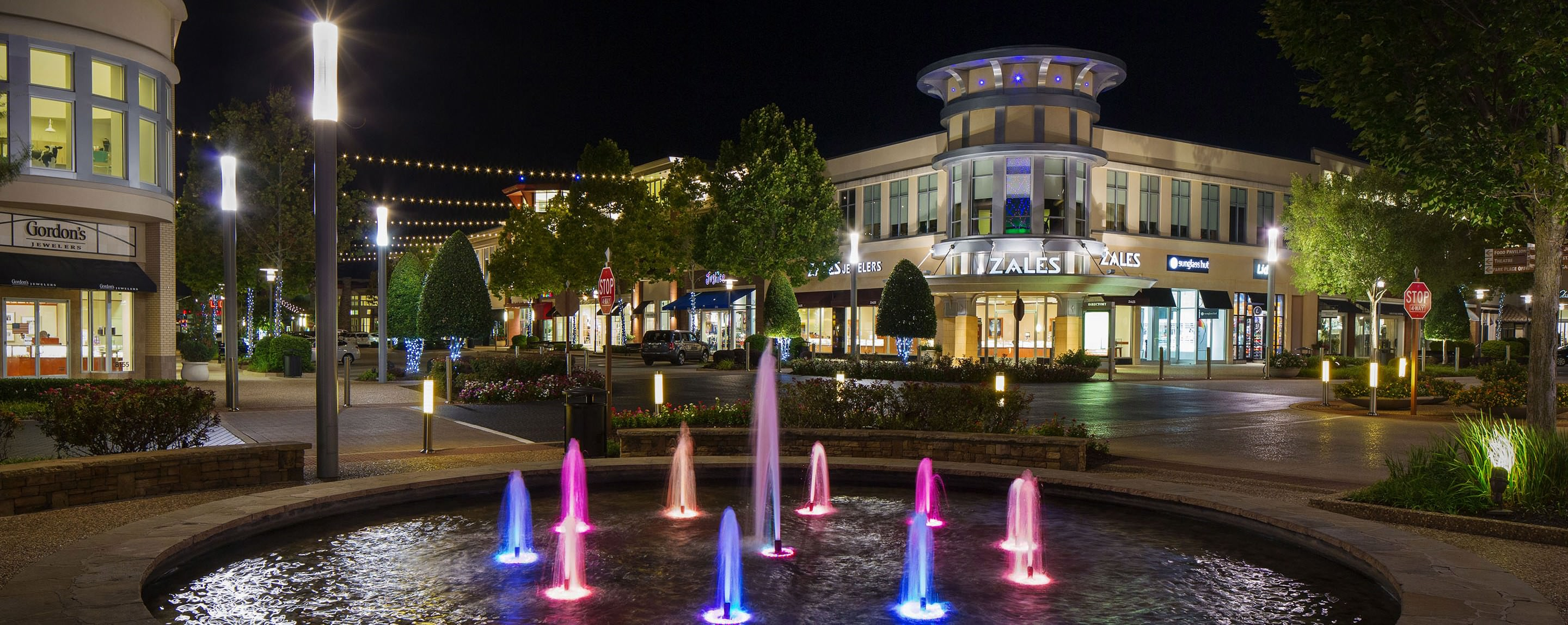 At night, the exterior of Pinnacle Hills Promenade is brightly lit by decorative lighting and storefronts.