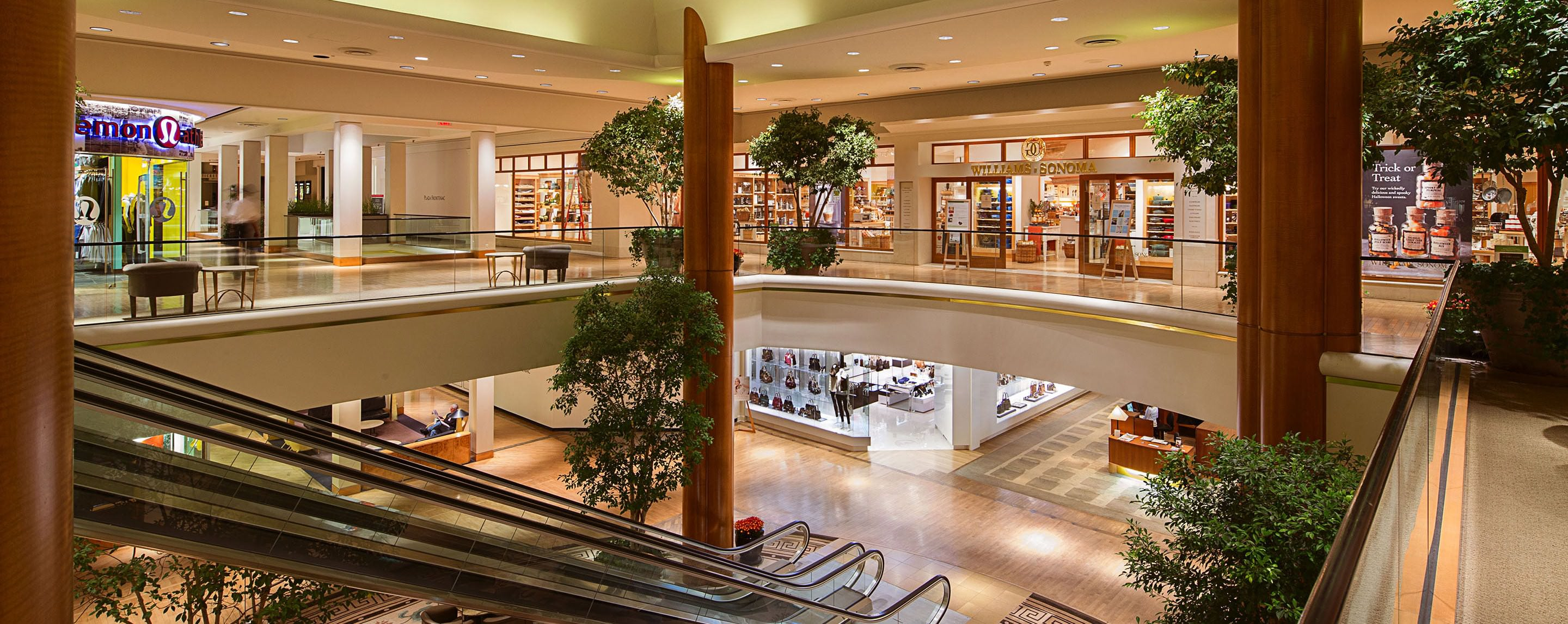 From the second level of Plaza Fontenac, you can see two levels of store fronts decorated with trees.