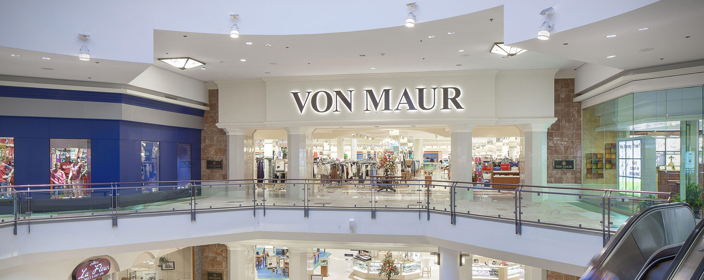 A brightly lit Von Maur department store entrance can be seen on the top level of the Quail Springs Mall.