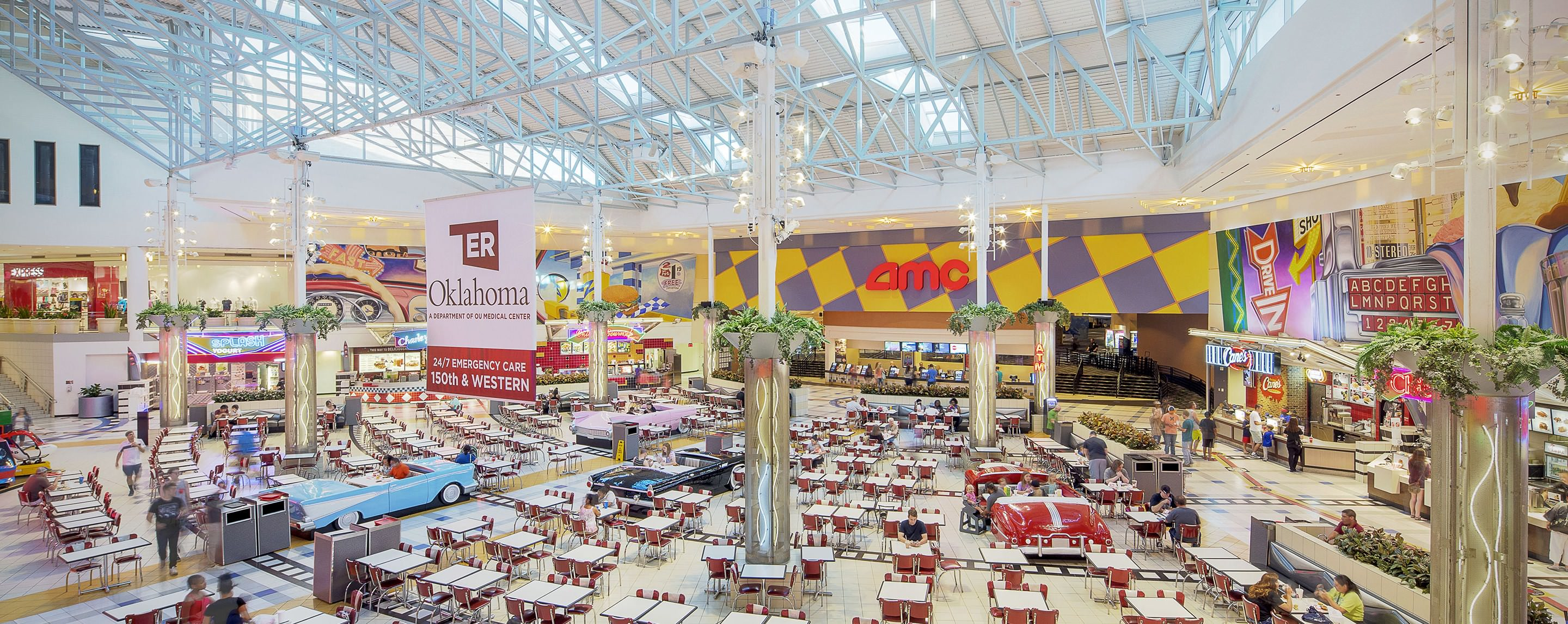 Visitors eat in the food court at Quail Springs Mall, surrounded by restaurants and the entrance to AMC Theatres.