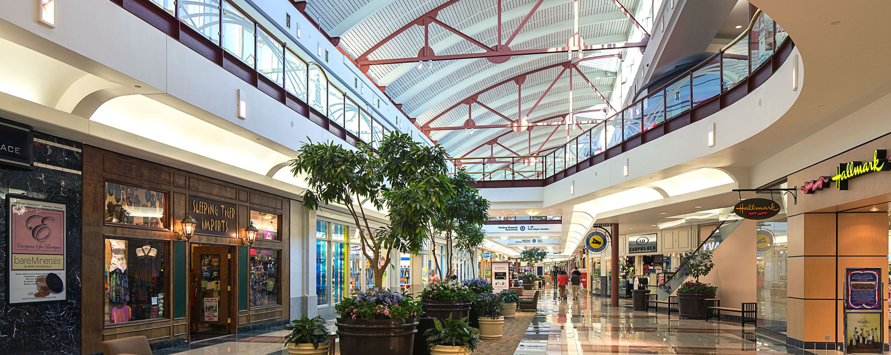 Shoppers walk around various shops and kiosks in an interior walkway at RiverTown Crossings.