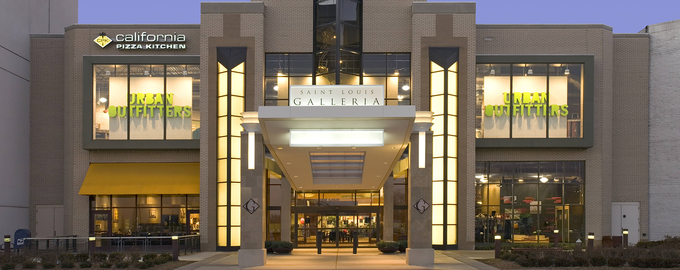 Urban Outfitters and California Pizza Kitchen can be seen through the brightly lit exterior entrance at Saint Louis Galleria.