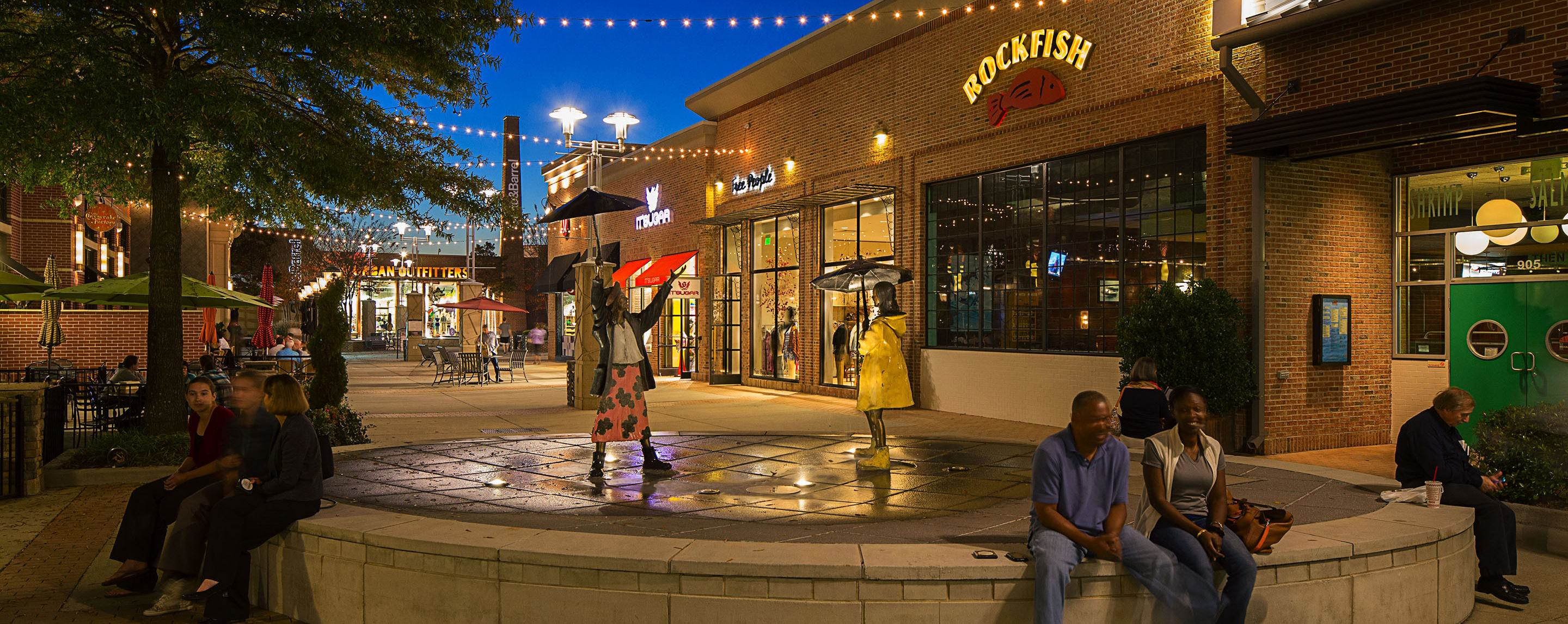 Shoppers take a break at The Streets at Southpoint  during dusk sitting on an outdoor decorative fountain.