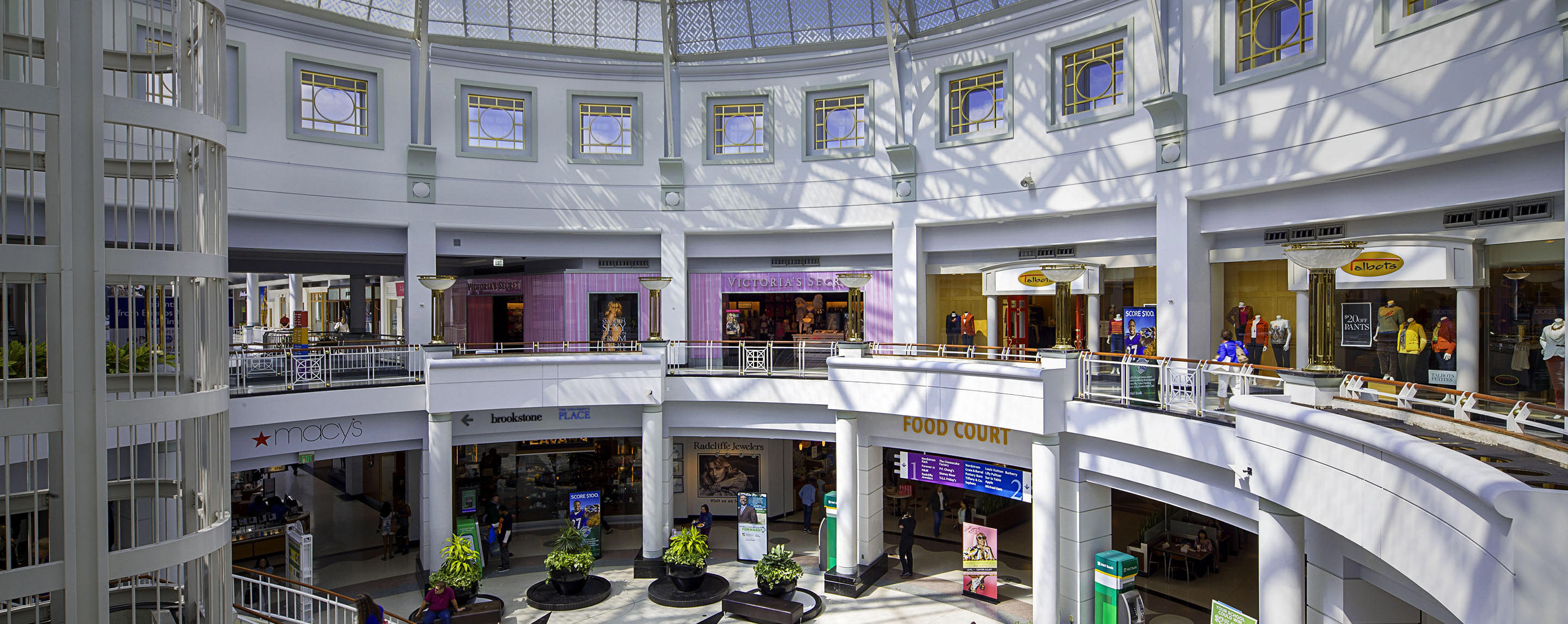 From the second floor of Towson Town Center you can see various storefronts and helpful signs to guide shoppers.