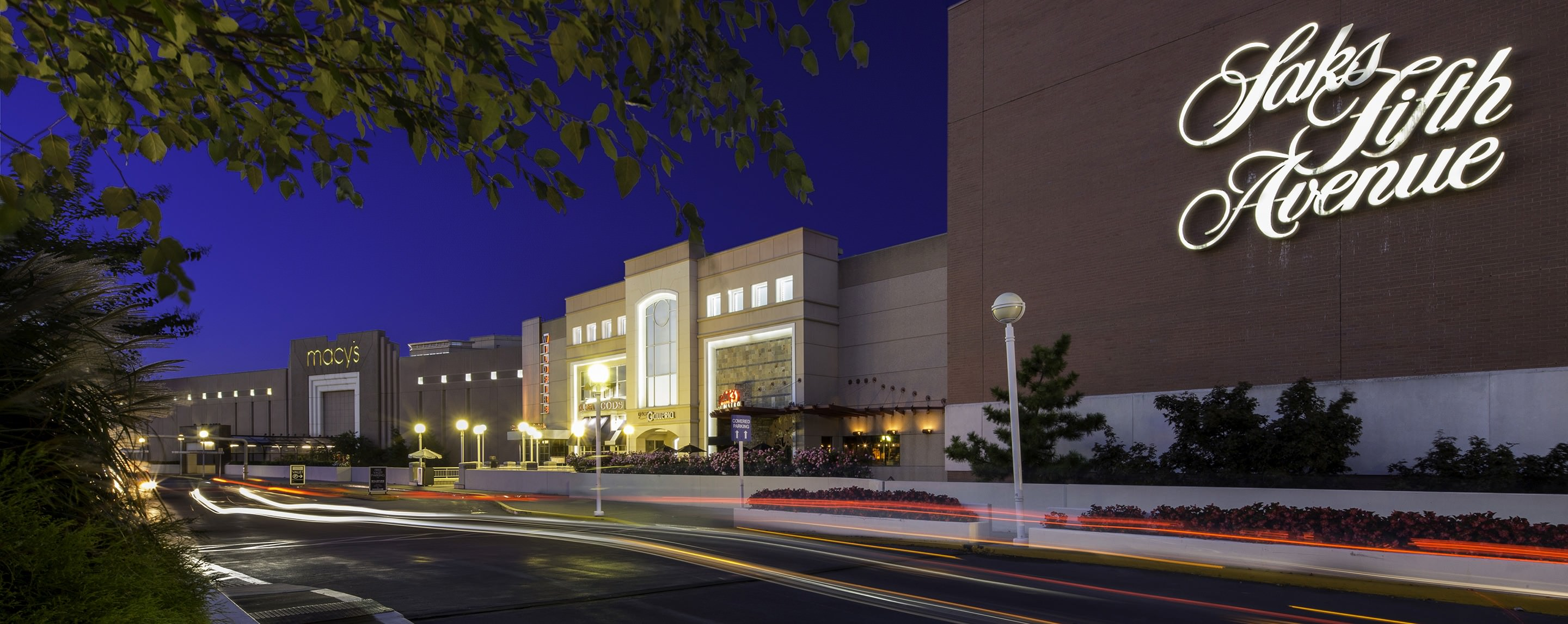 At night, an entrance to Tysons Galleria is illuminated by lights in between two of the centers anchor stores.