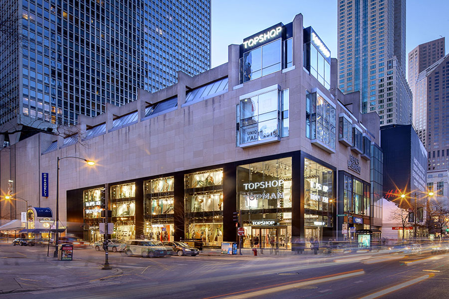 At dusk, the shops at 830 N Michigan Ave shine brightly, including Topshop and Uniqlo.